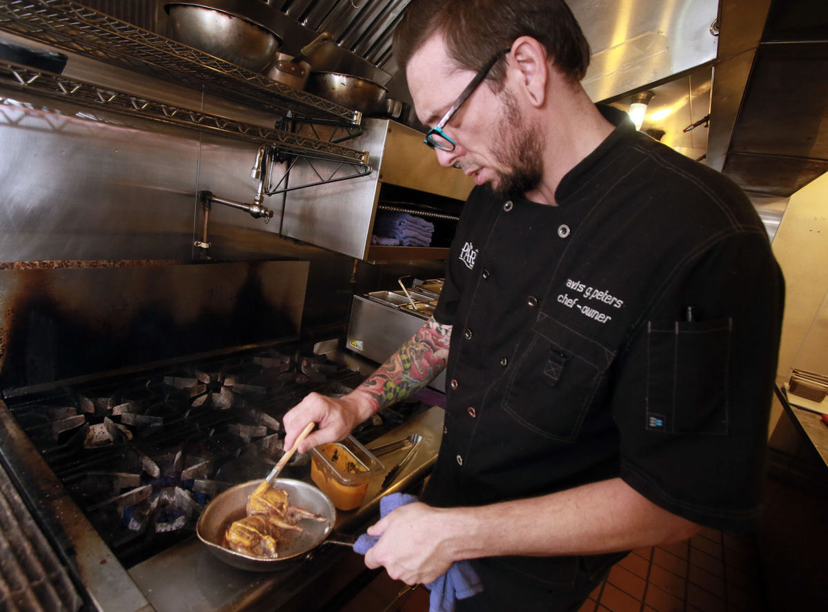 """RON MEDVESCEK / ARIZONA DAILY STAR Chef Travis Peters works on his Alabama Quail dish at The Parish gastropub. """"I want everything to have a reason Peter says."""