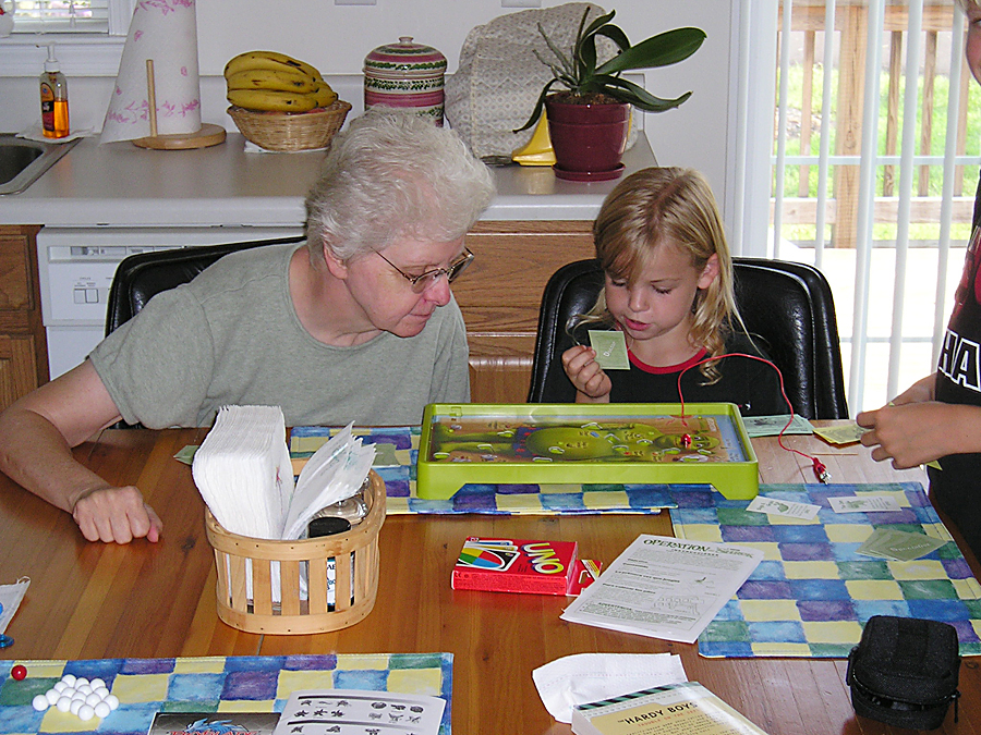 Diane and her grandchildren, Trevor and Kelsey, playing board games at the dining table
