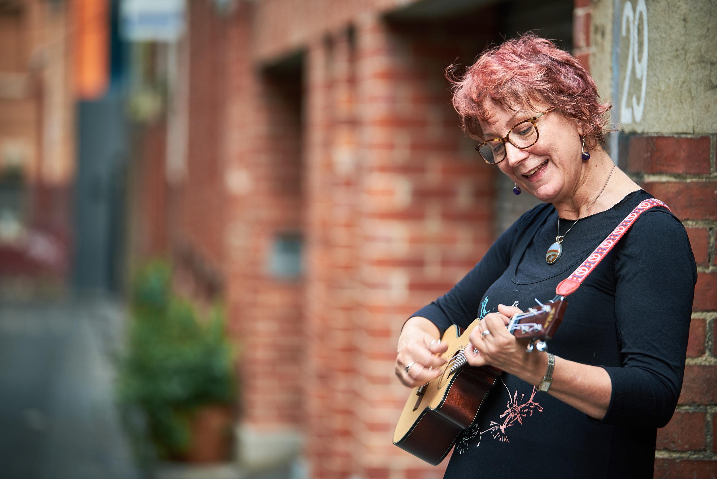 Portrait of Tina playing ukulele in Melbourne laneway