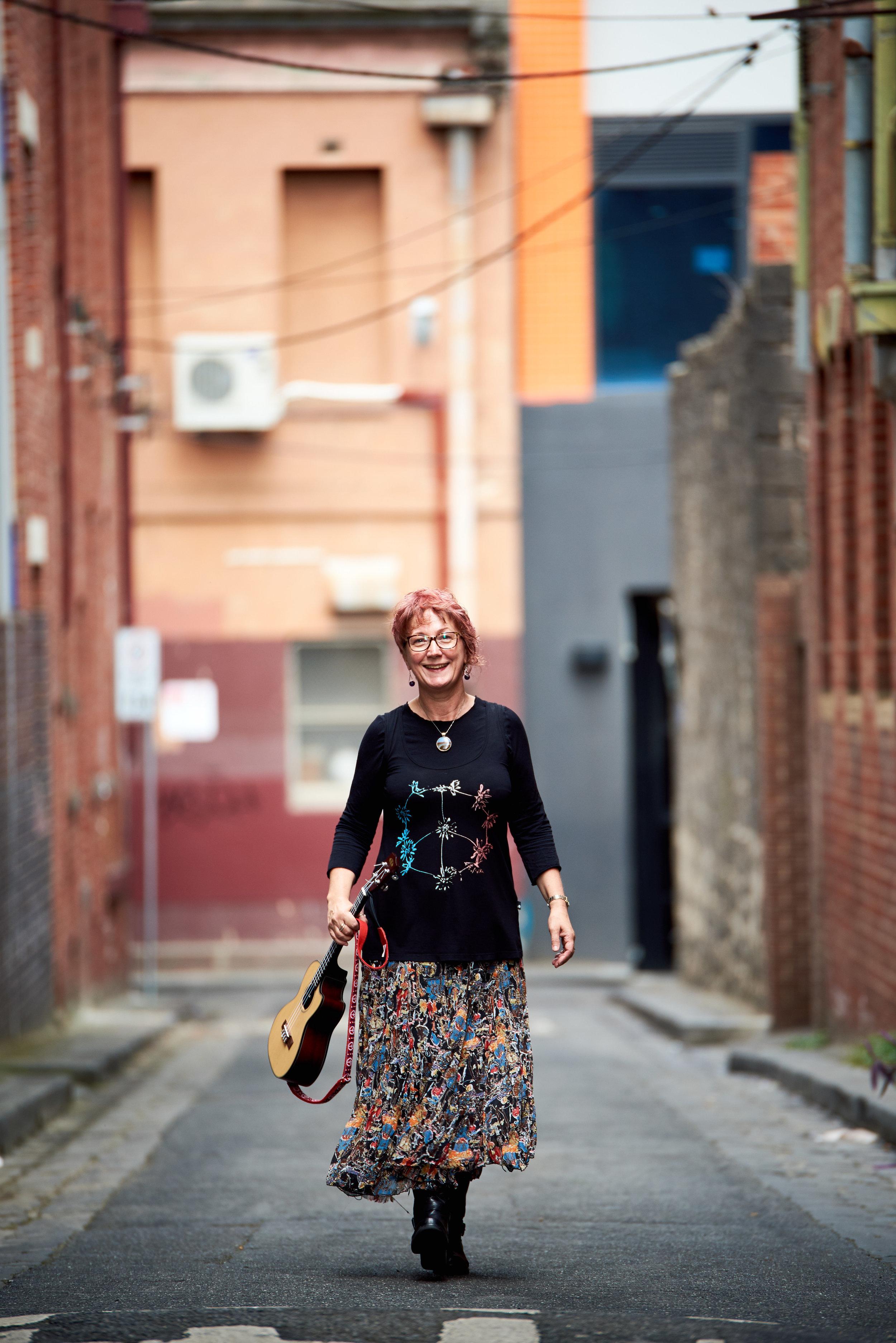 Portrait of Tina walking in Melbourne laneway holding ukulele