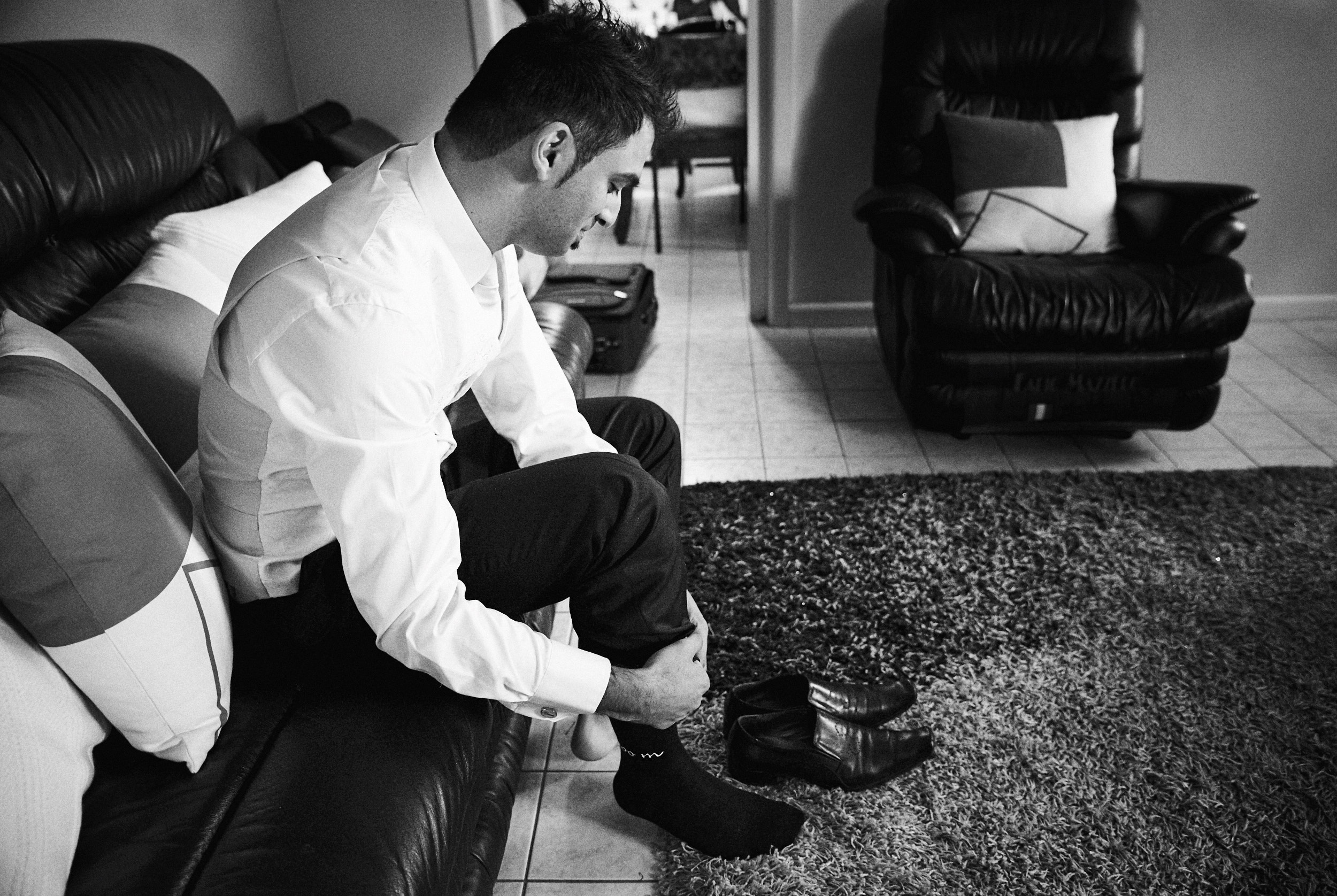 Groom putting on socks and shoes