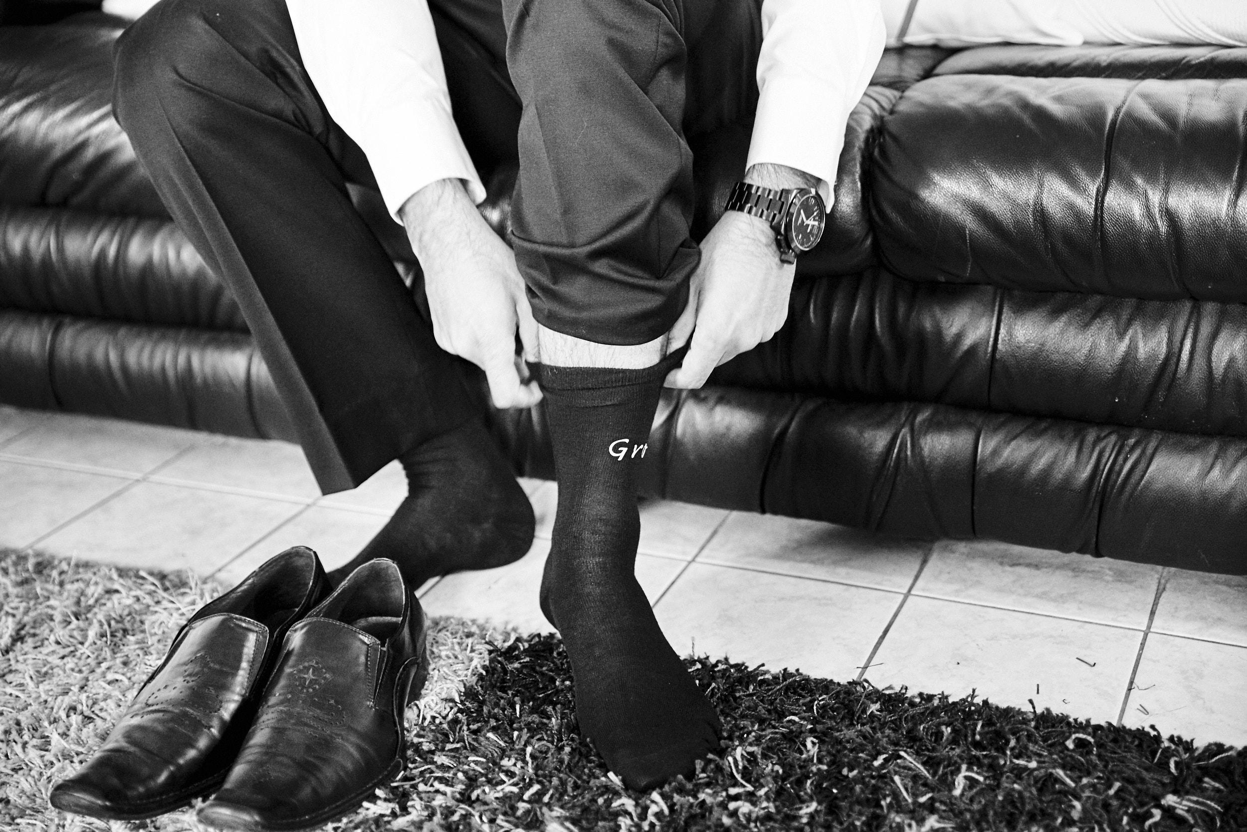 Groom pulling up his socks