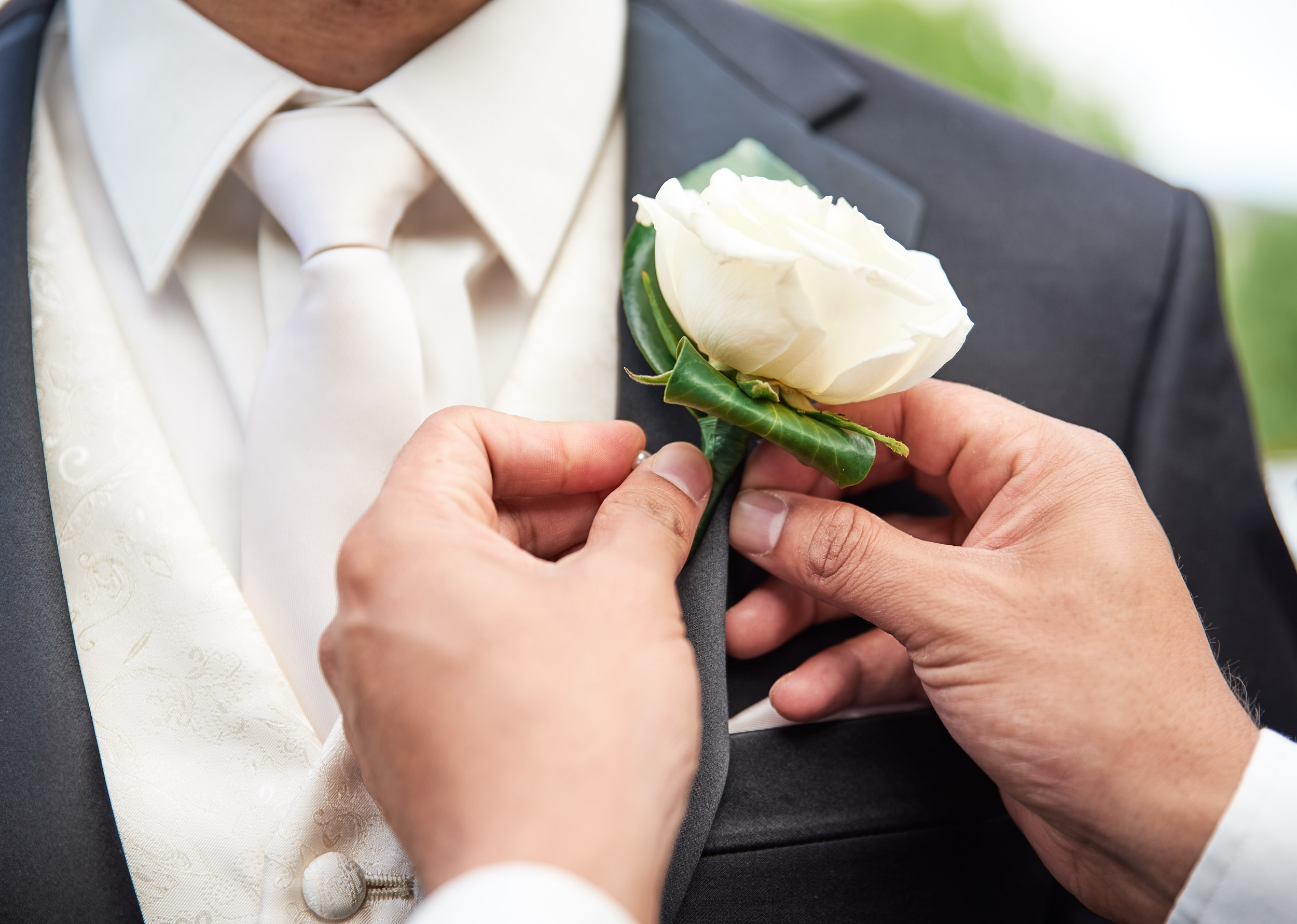 Attaching boutonniere to groom