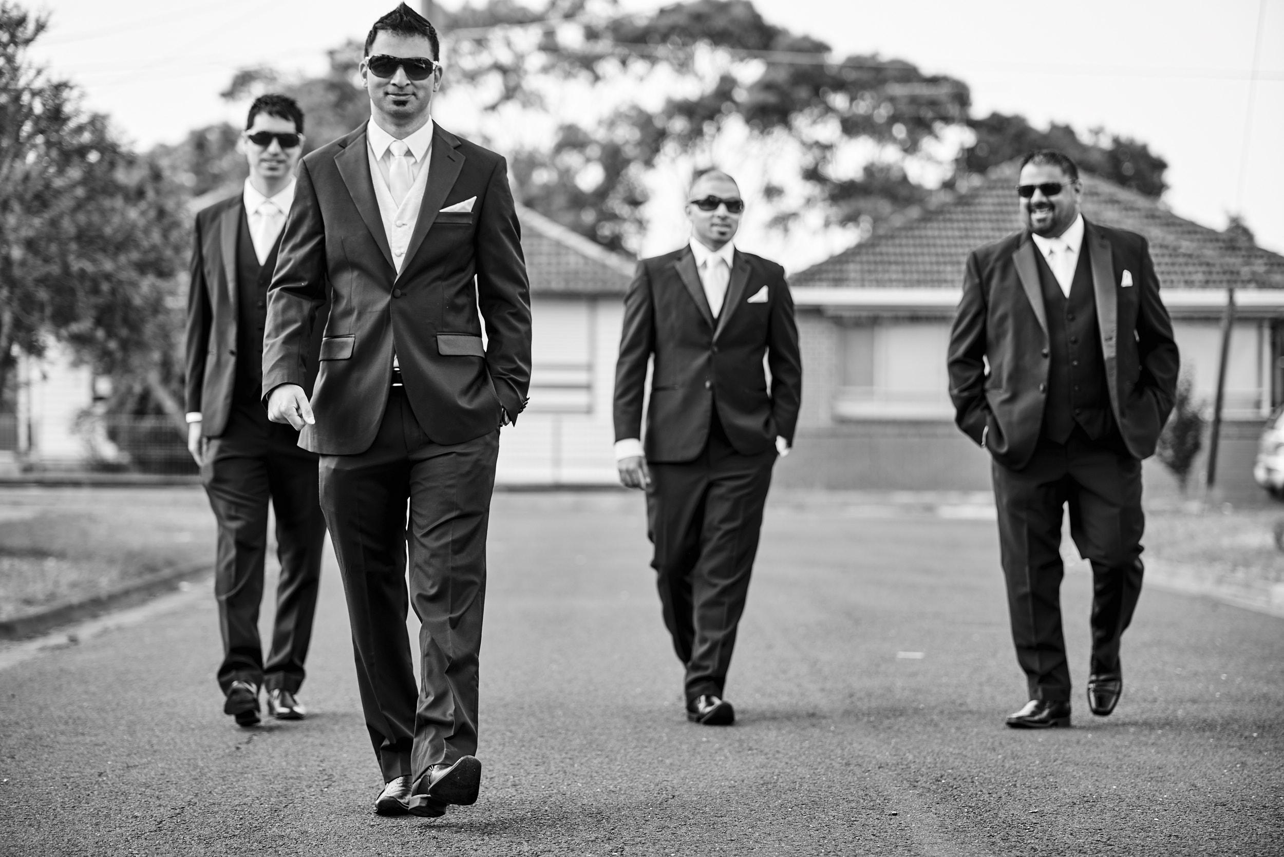 Groom and groomsmen walking down street