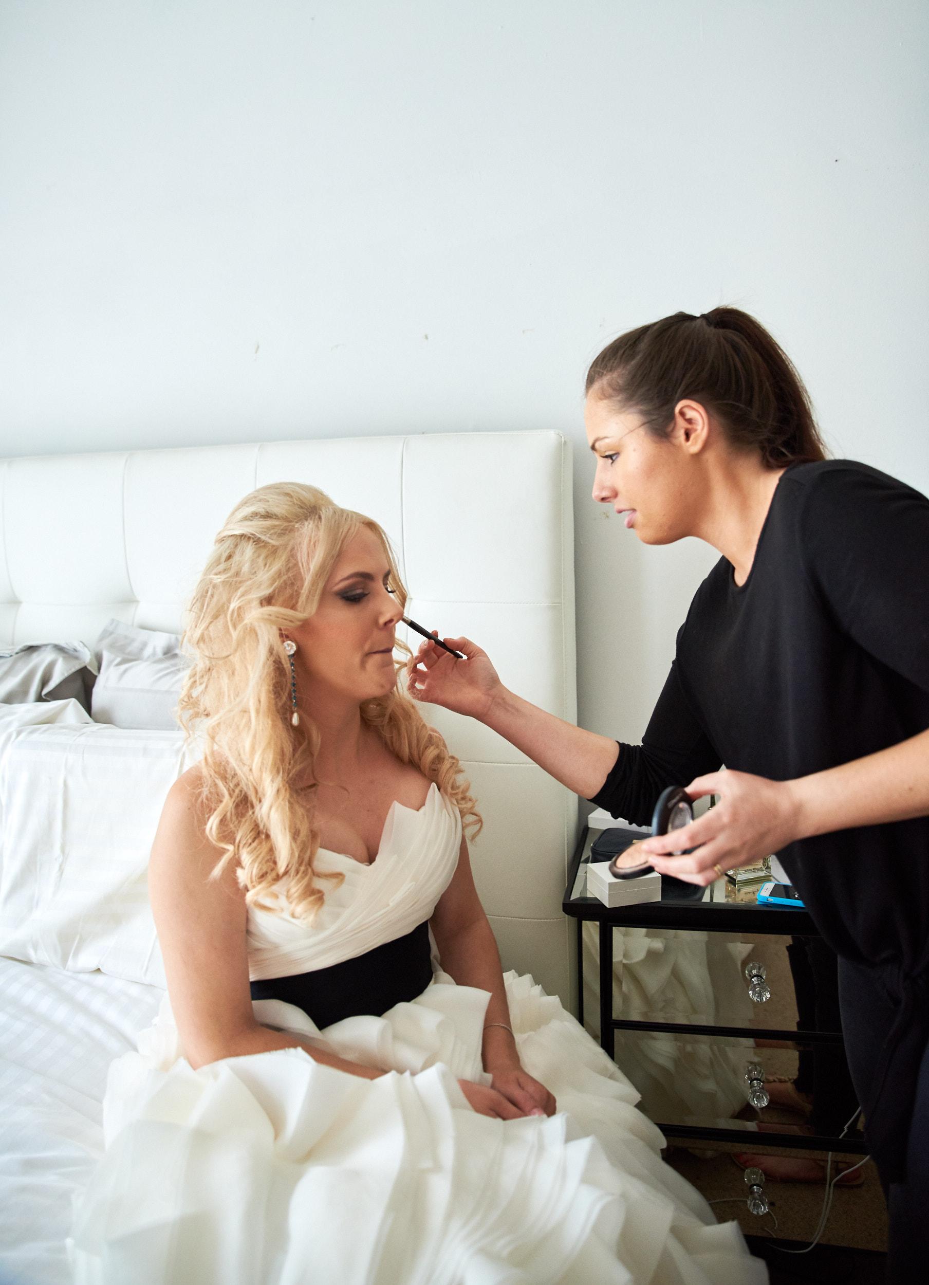 Makeup artist applying makeup to bride