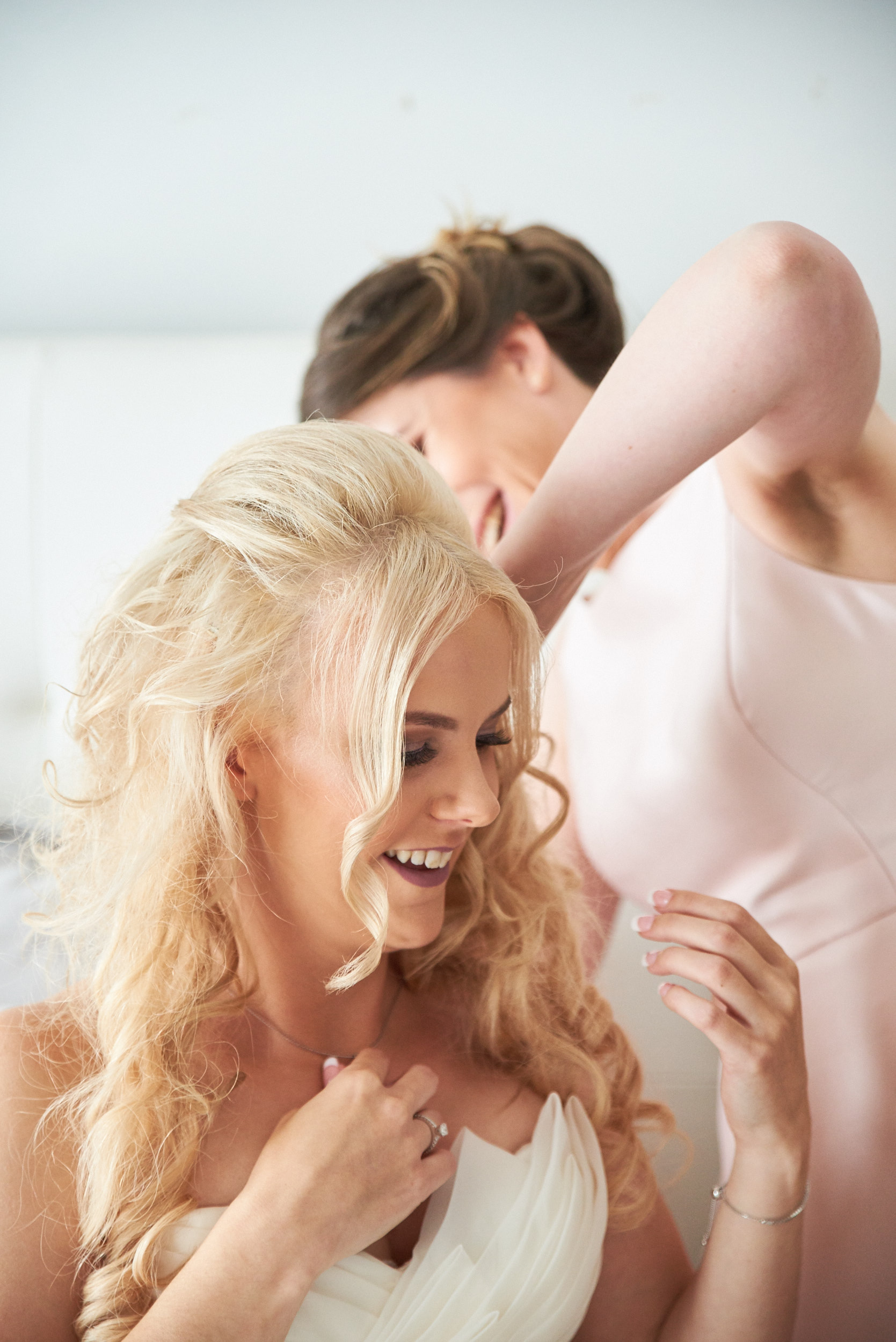 Bridesmaid helping bride to put on necklace