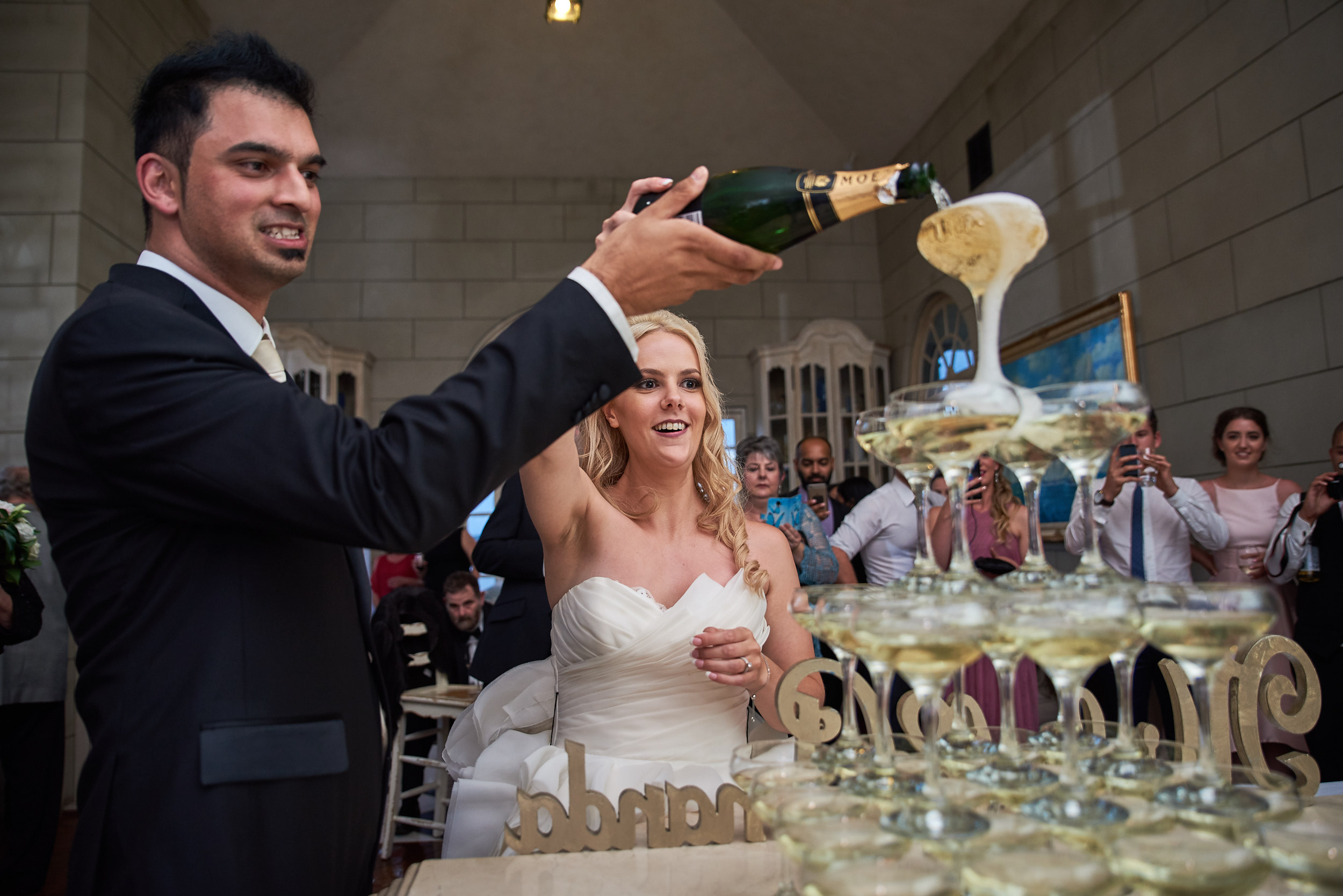 Bride and groom pouring champagne into pyramid of glasses at Campbell Point House