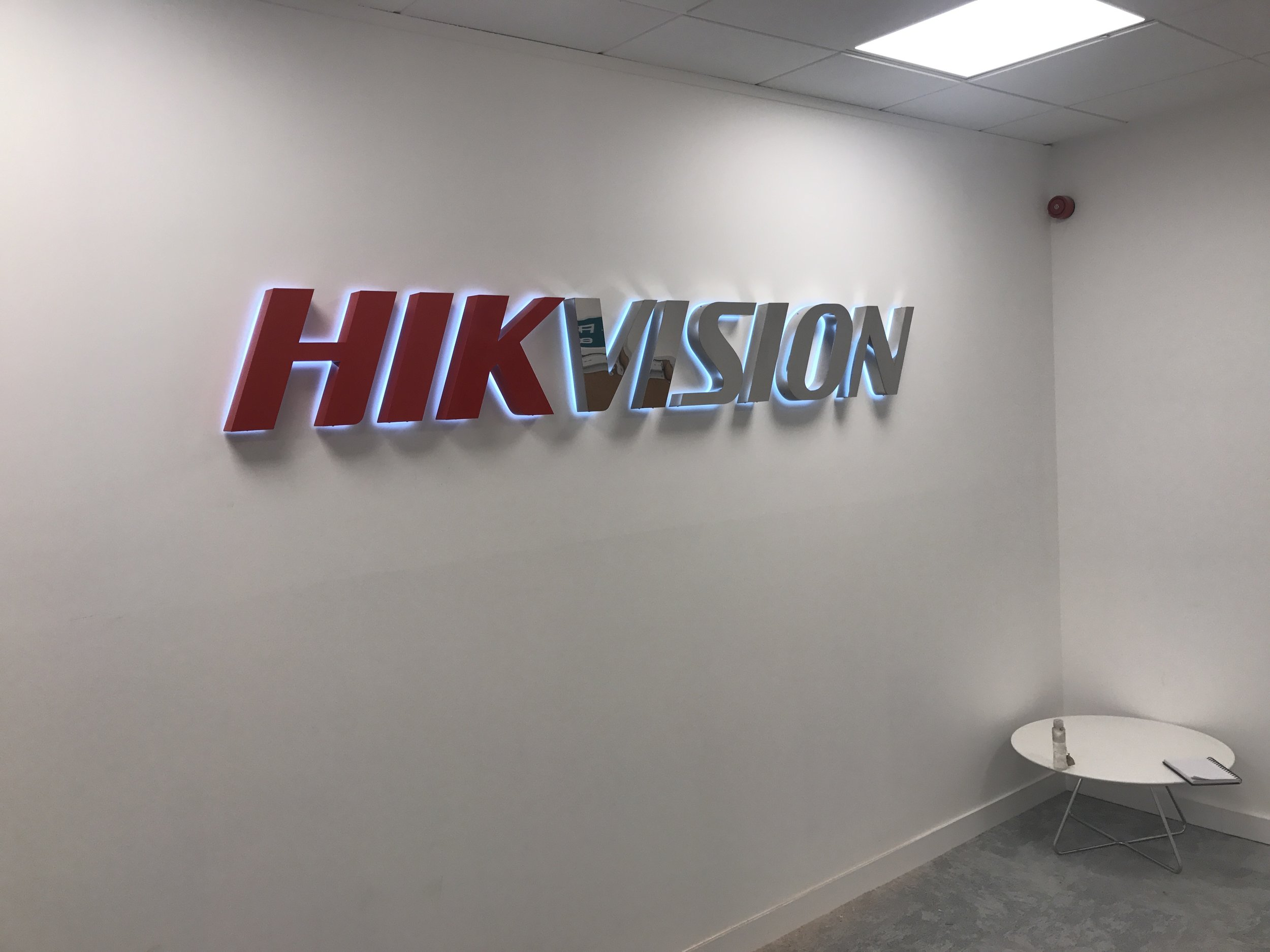 Built Up Halo Illuminated Letters.   Built up halo illuminated letters installed to an internal office space wall. The first half of the letters were powder coated a standard RAL colour for 'HIK' and the second half 'VISION' given a polished stainless steel finish.
