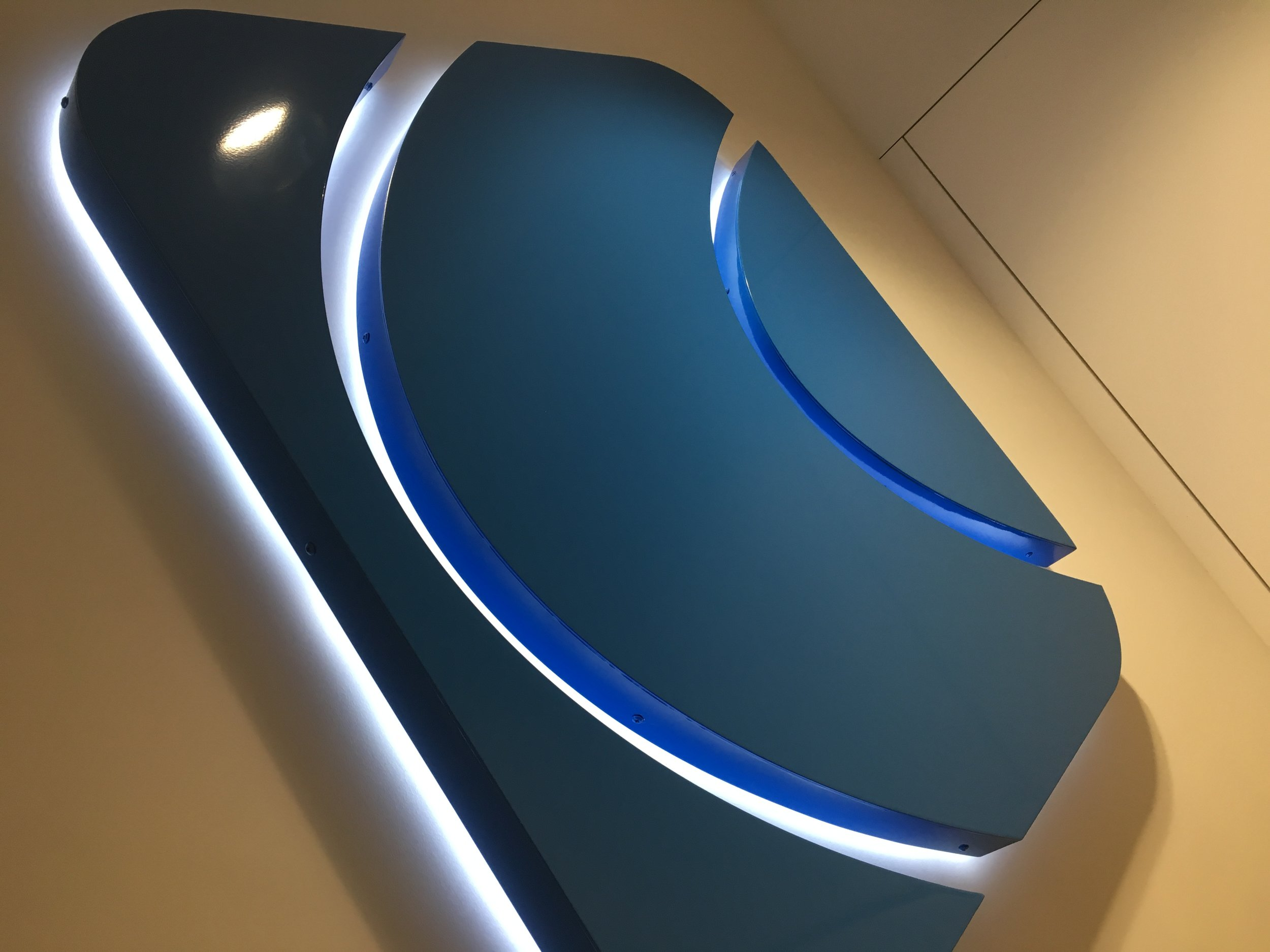 Built Up - Halo Illuminated Logo.   Built up, powder coated individual built up letters to create company logo shape, letters were supplied and installed with foam back trays and LED's to give a face free of fixings and halo illumination.
