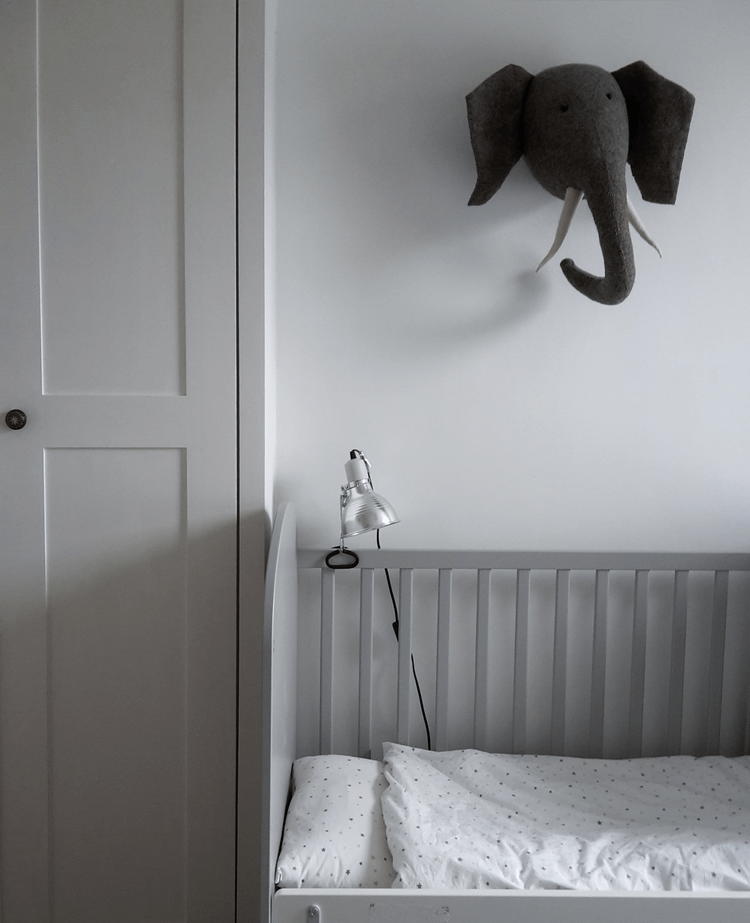 Childrens room with bed, lamp and elephant wall art