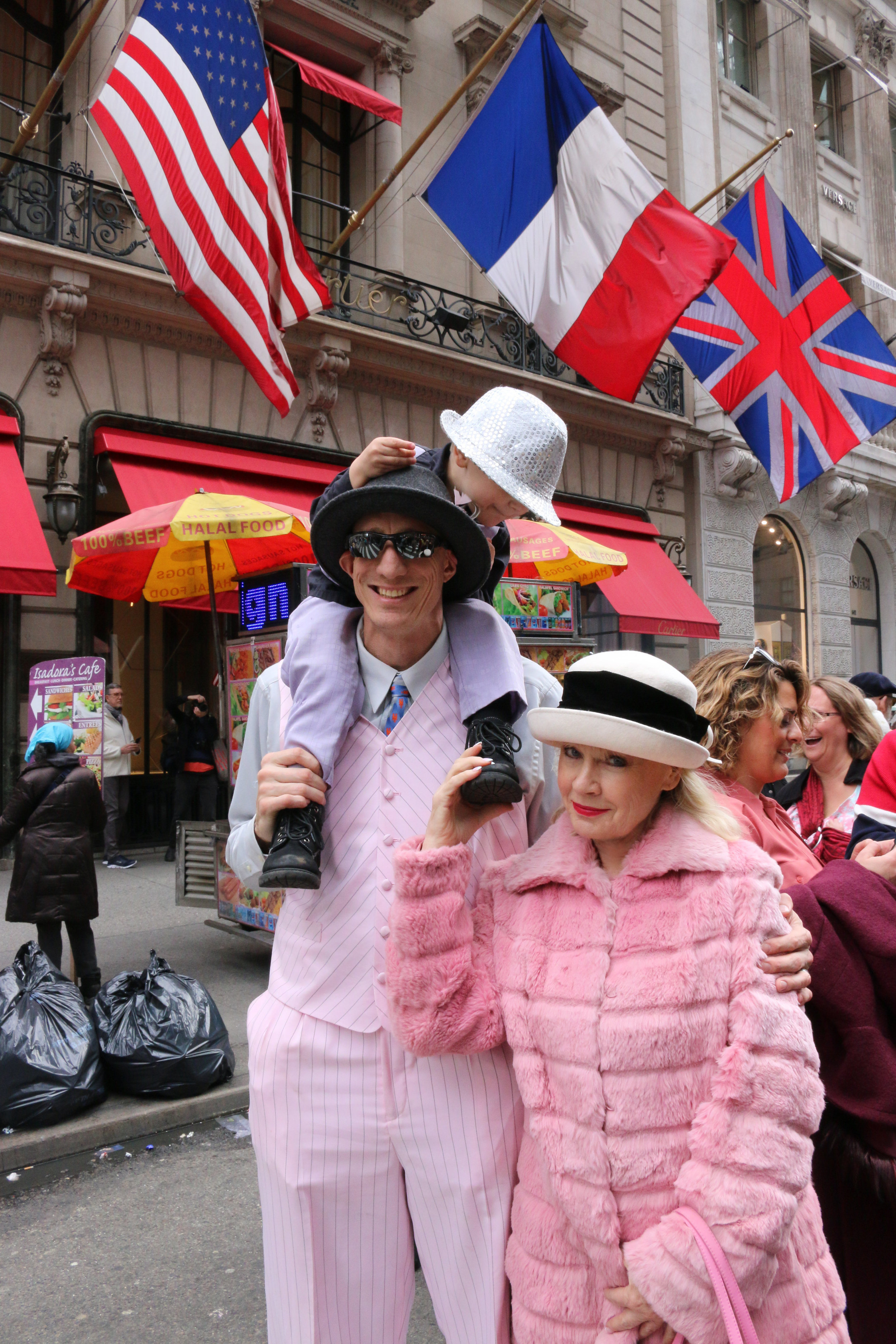 Lucille Khornak poses for a photo with a father son duo at the 2018 Easter Parade in New York City