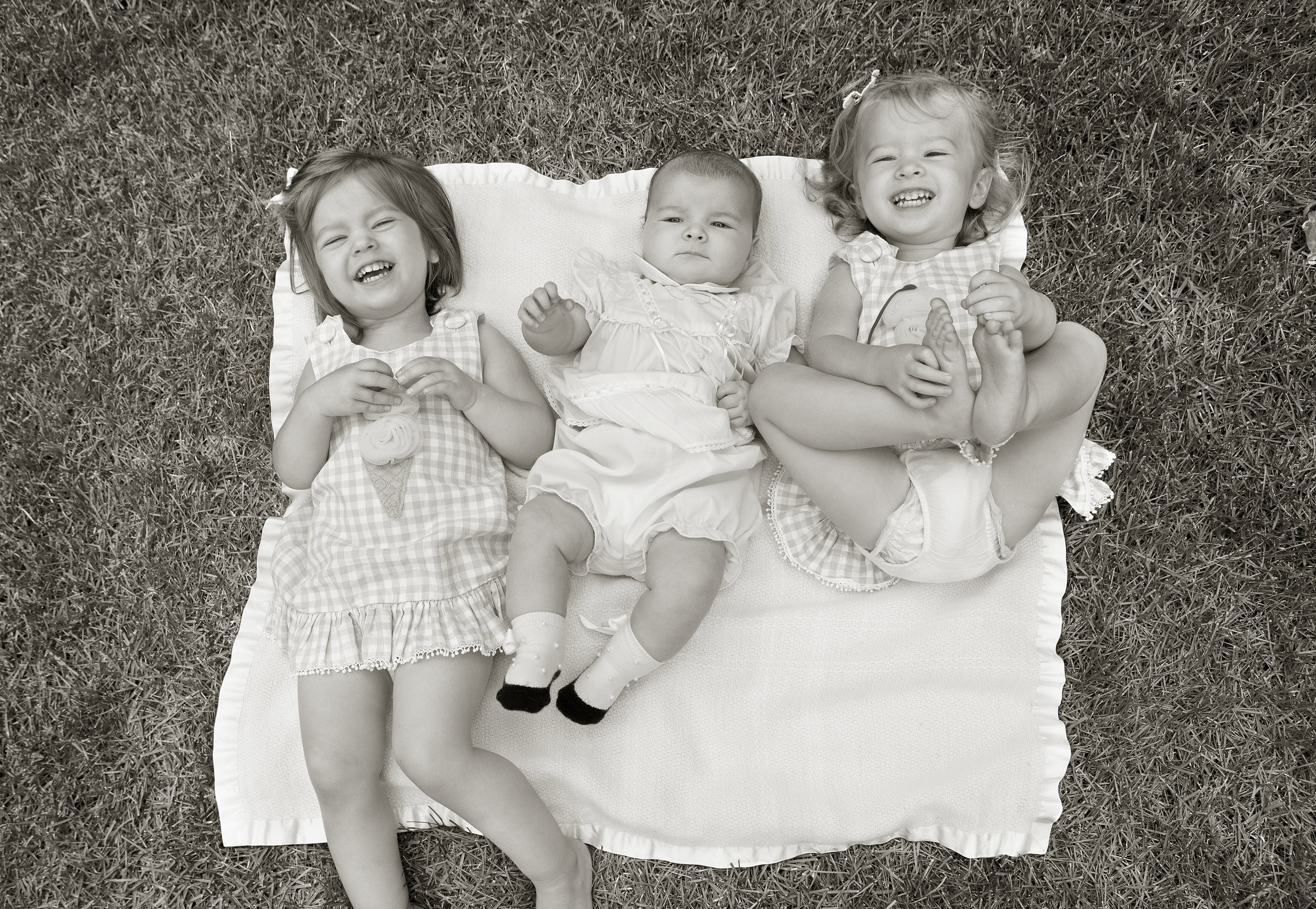 Iconic photo of two older sisters enjoying a moment of whimsy with their baby sister. Photo by Lucille Khornak.
