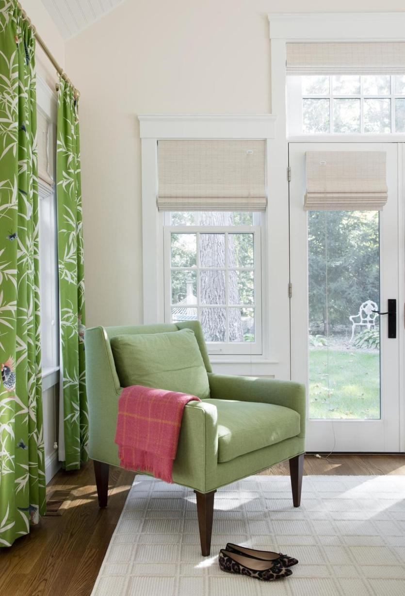 """The master bedroom drapery fabric featuring tropical birds is Bamboo Grove from Bob Collins & Sons. """"The neutral rug has a pattern that adds to the room, but not too much,"""" Emily says."""