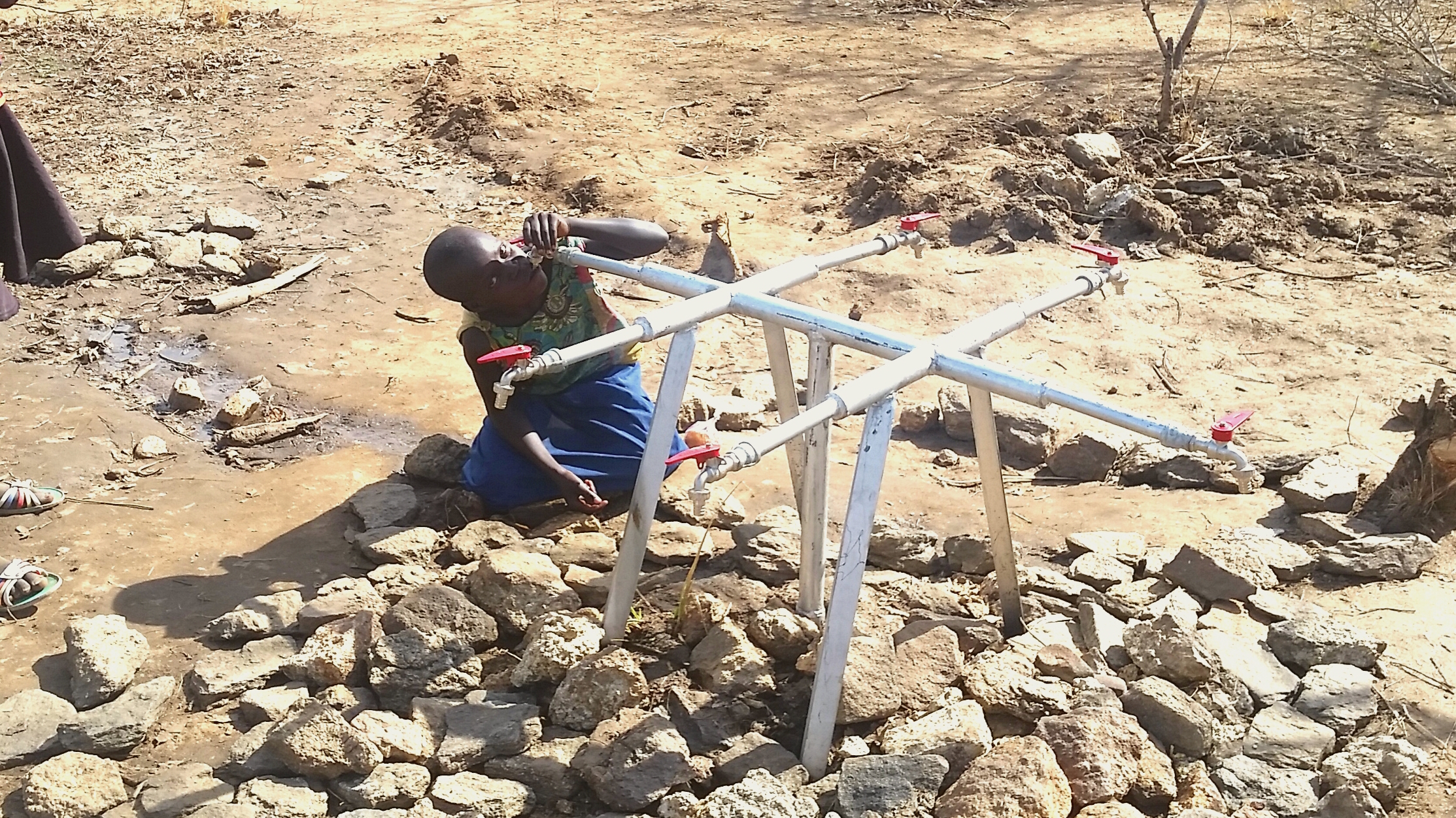 This young girl desperately sucks on an empty water pipe, as Imvepi Camp goes on two long days without any water.