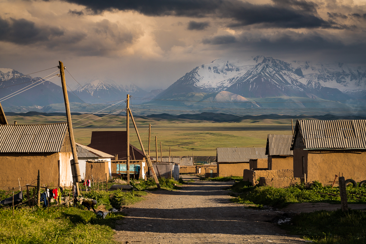 The main road in Sary mogul village with the Pamir mountains in the background
