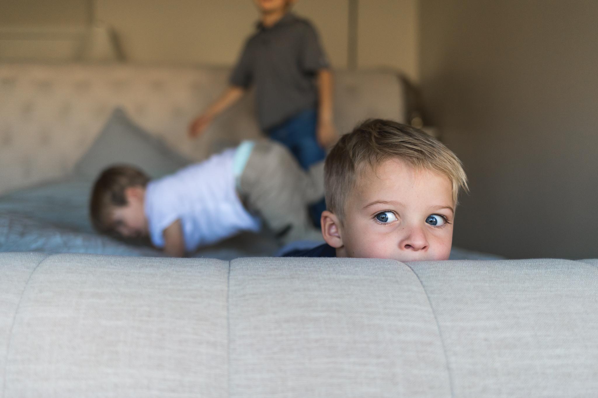 Blue eyed boy peeks over bed - Lifestyle photography Utah