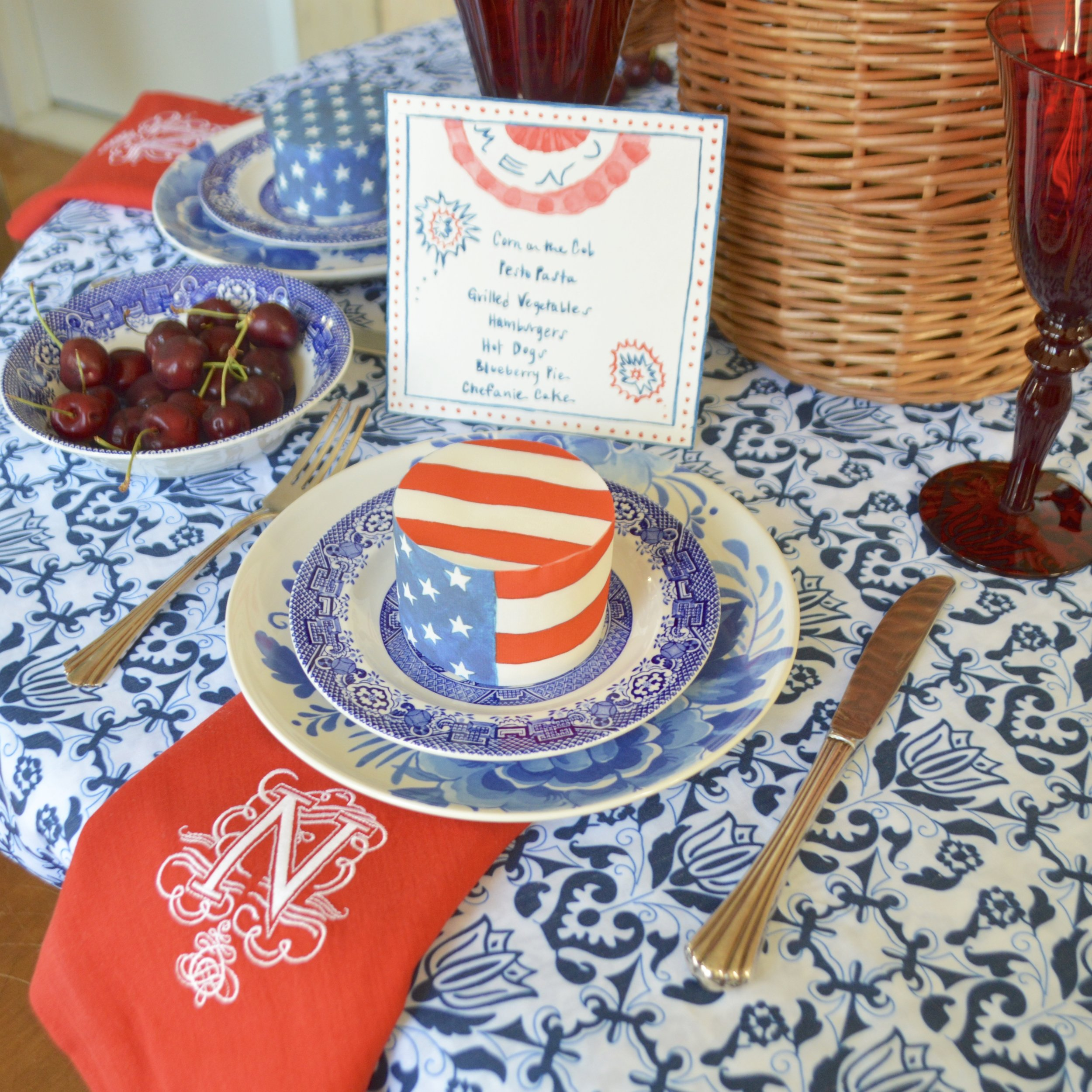 Mini Cake Wrapped in  Flag Chefanie Sheets , over  Blue & White Tablecloth , with  Custom Embroidered Napkins