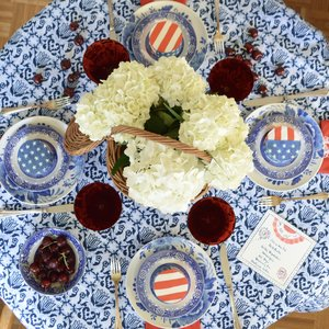 Four-Person July 4 Table with  Blue & White Tablecloth ,  Custom Embroidered Napkins , White Hydrangeas in  Wicker Basket , and Personalized Cakes with  Flag Chefanie Sheets