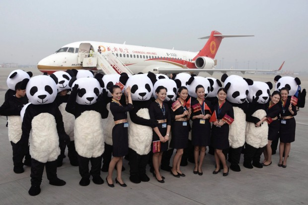 People in panda costumes pose with flight attendants in front of a Chengdu Airlines. Photo credit: AP.
