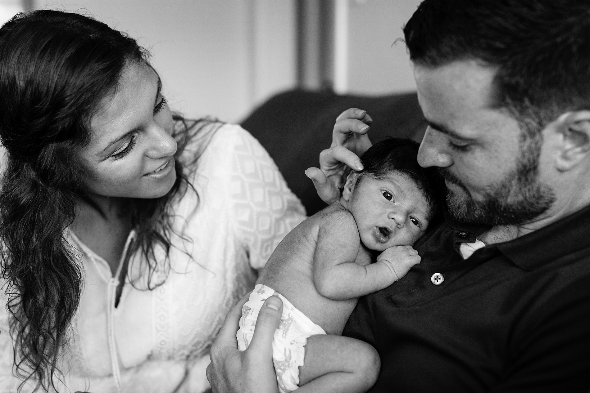 new mother and father admire adorable newborn baby
