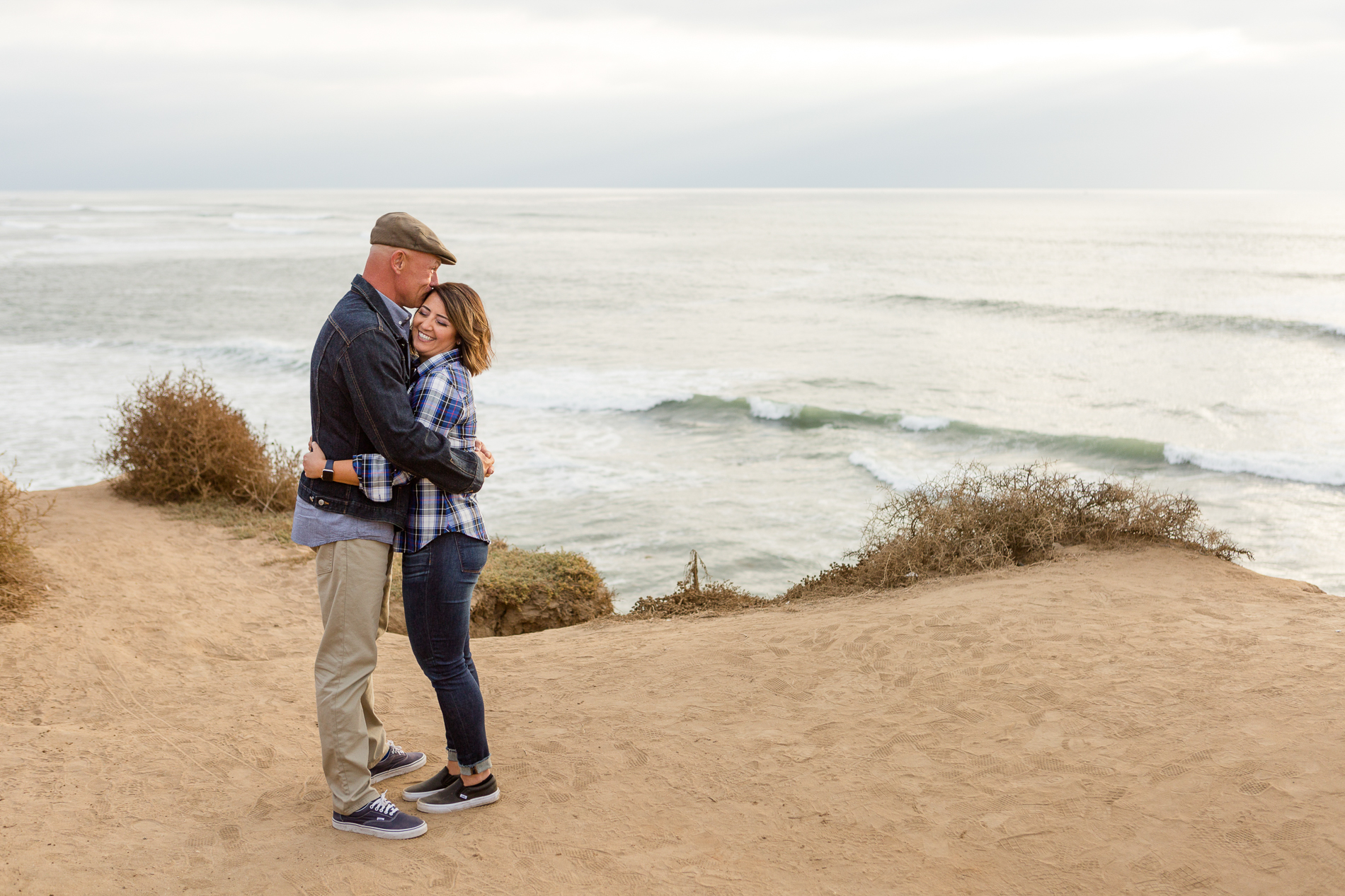 couple hugging at sunset cliffs San Diego
