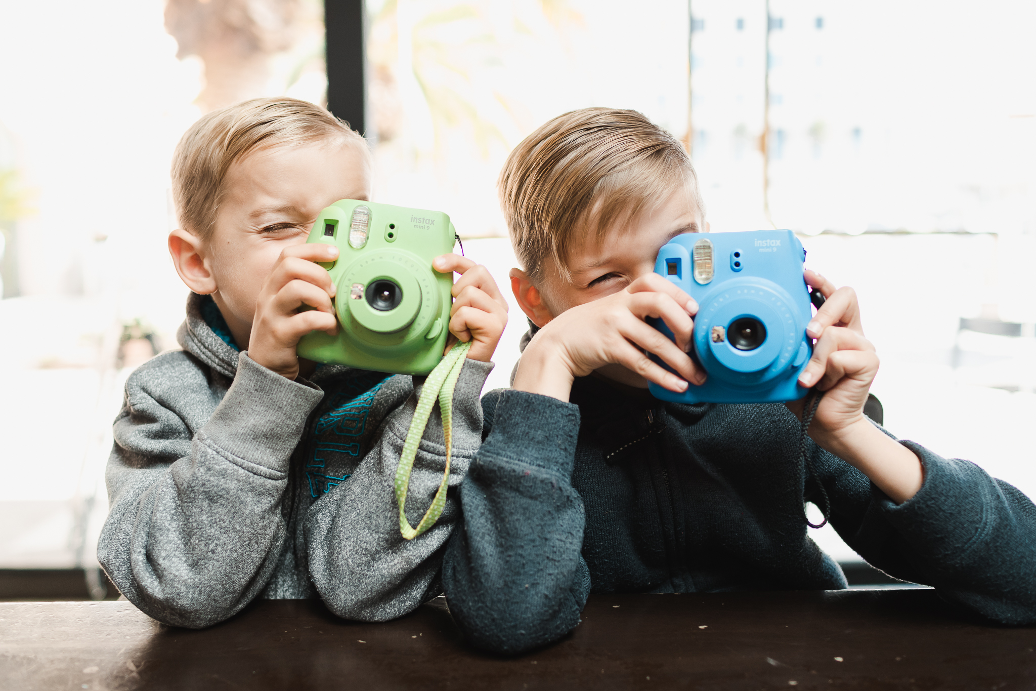 TWO BOYS HOLDING FUJI INSTAX CAMERAS UP READY TO TAKE A PHOTO