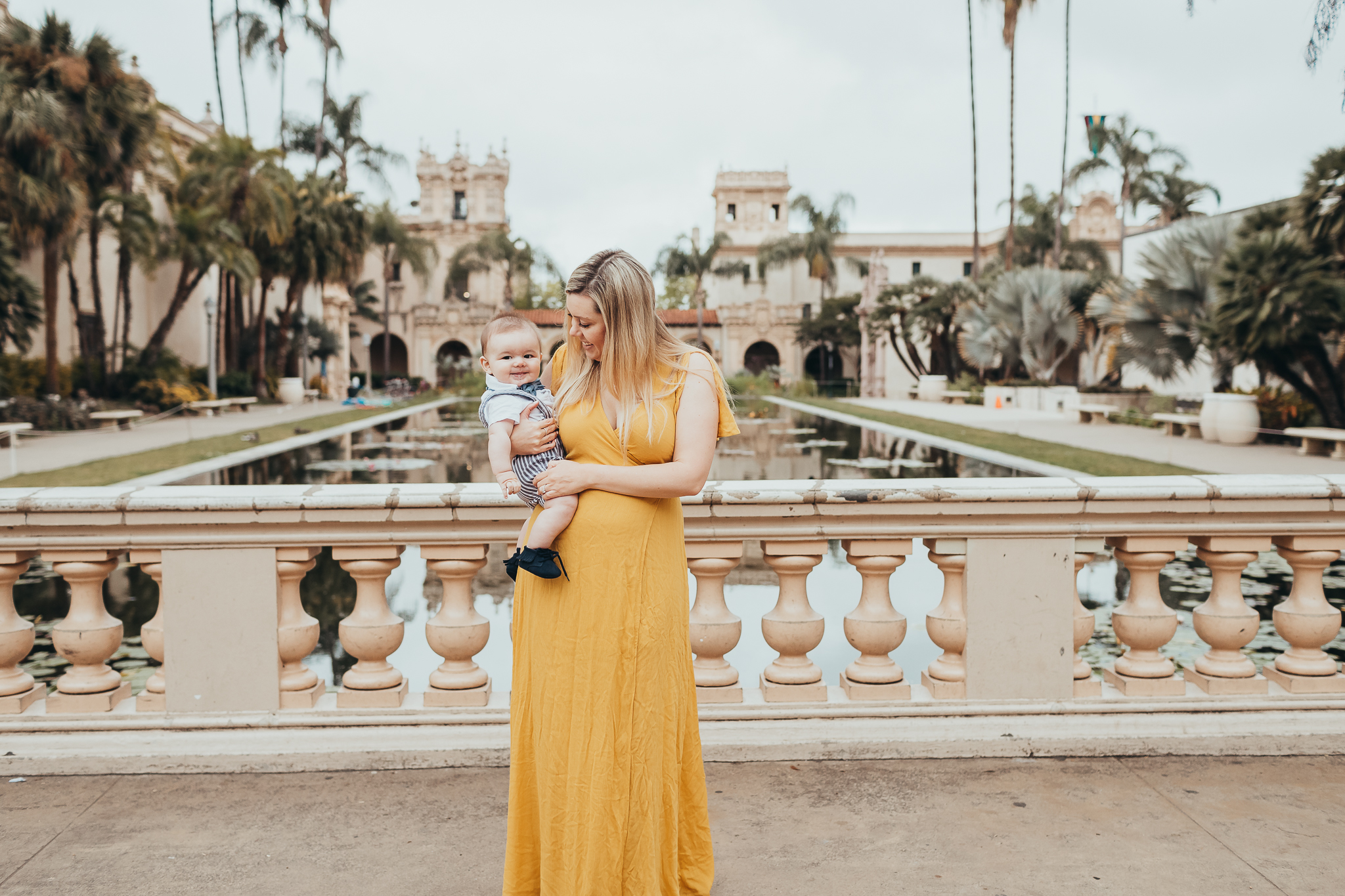 mom holding baby at the reflection pool in Balboa Park in San Diego.