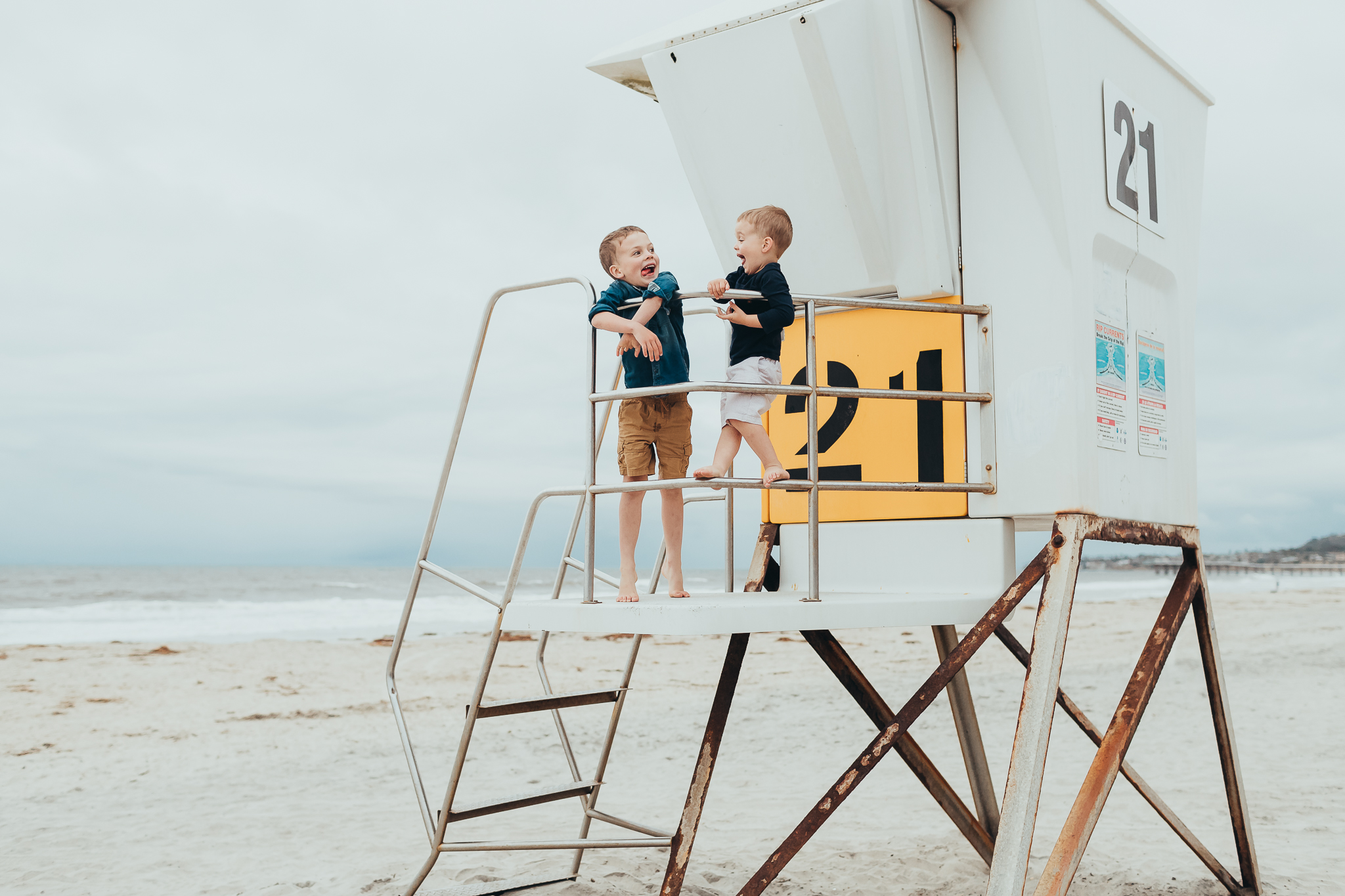 two brothers making silly faces on the beach