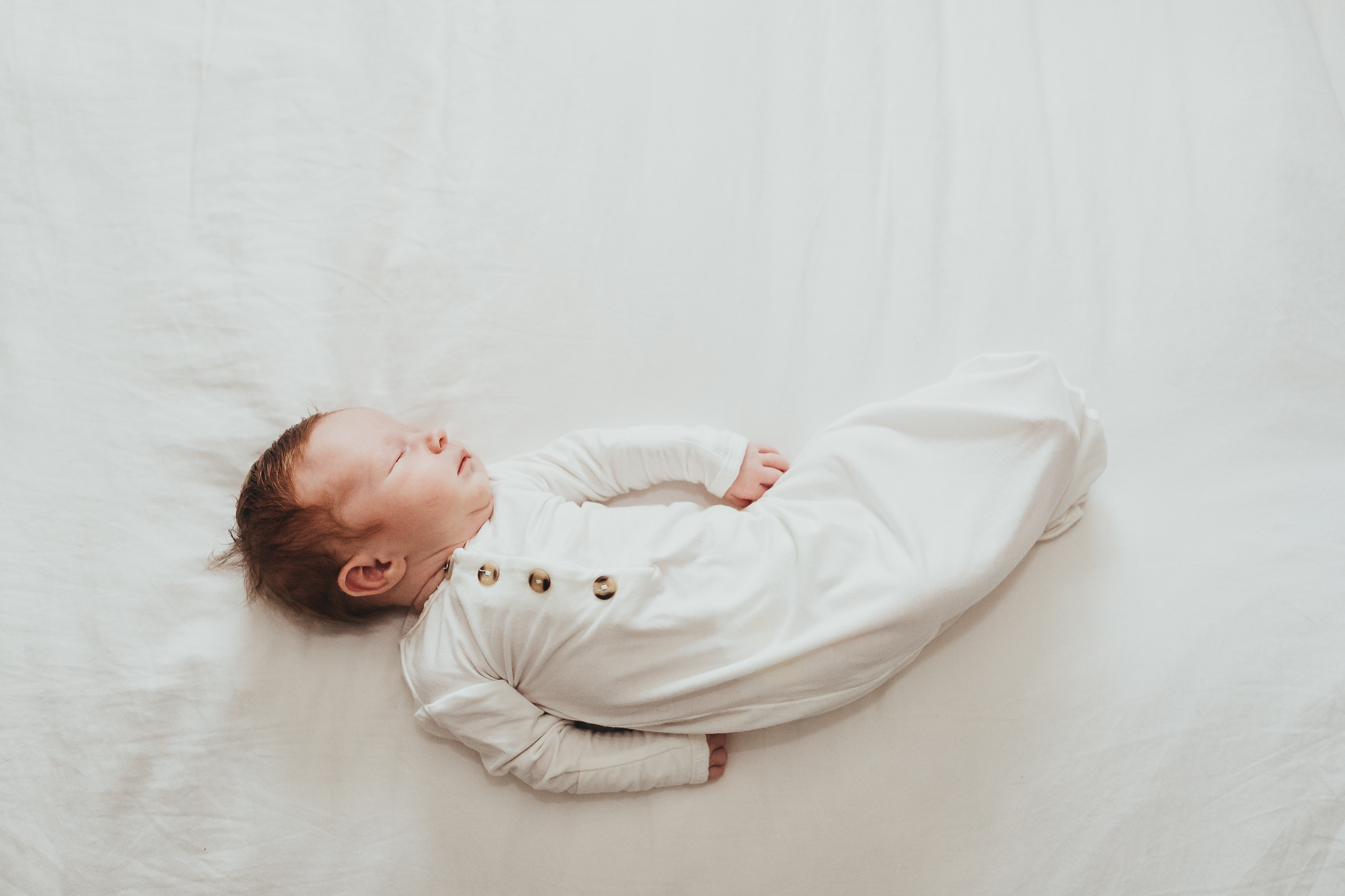 newborn baby laying on bed in sweet white onesie