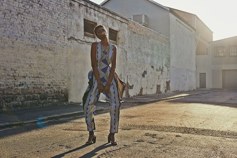 Black, white, blue and yellow print jumpsuit,  Leigh Schubert ; blue leather sling bag with gold detail,  Kokomo