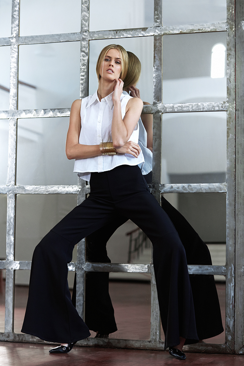 White sleeveless crop shirt, Amanda Laird Cherry ; black bell trousers, Michael Maven ; gold cuff, Vikki-Lou