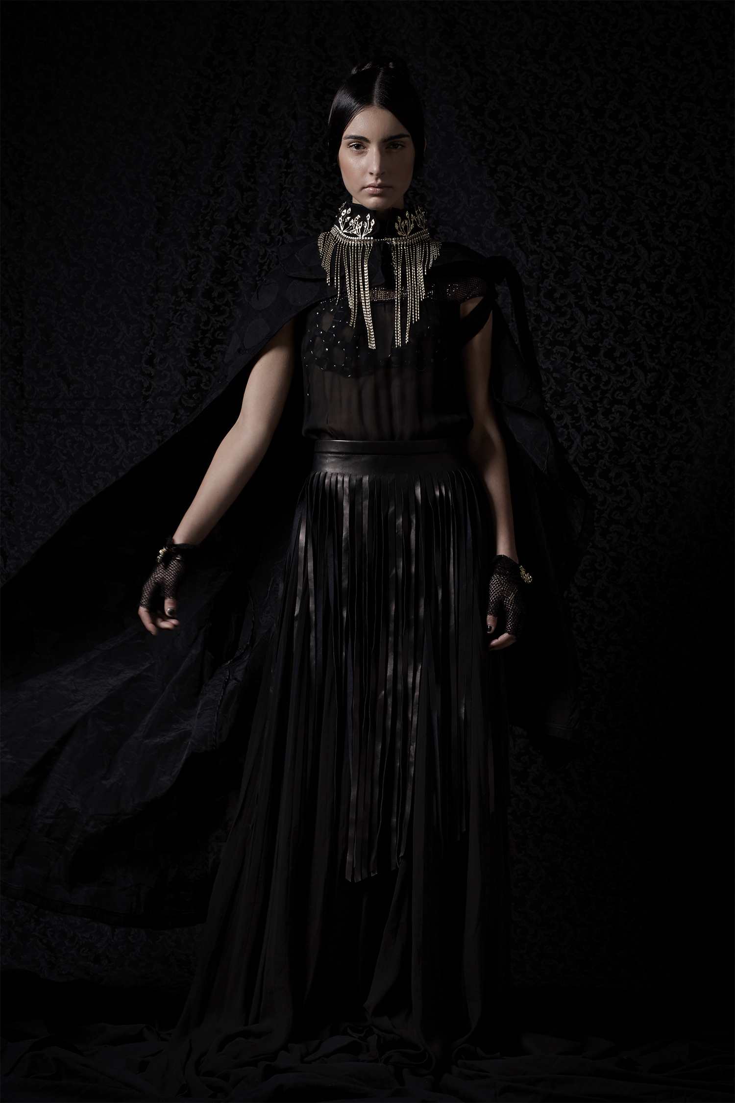 Black dress, Luigi Borbone; black cape, Yojiro Kake; black leather and metal bra and leather fringe skirt, Zora Romanska; crown (used as a collar), Vittorio Ceccoli Jewelry