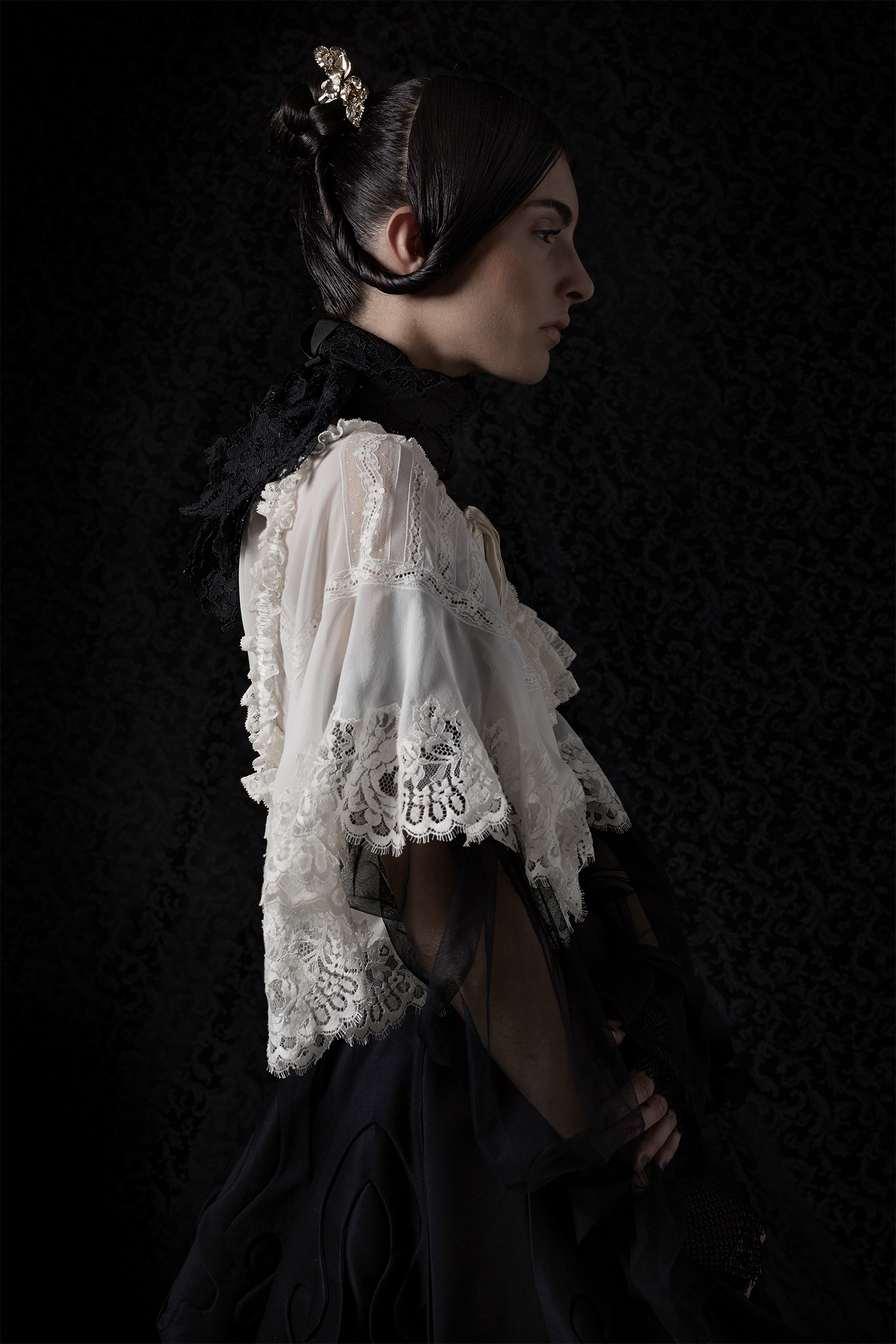 White blouse with lace detail, Annagiulia Firenze; black skirt, Sergiu-Marian Bechian; hair accessory, Vittorio Ceccoli Jewelry; black lace (used as a neckpiece), Giada Curti