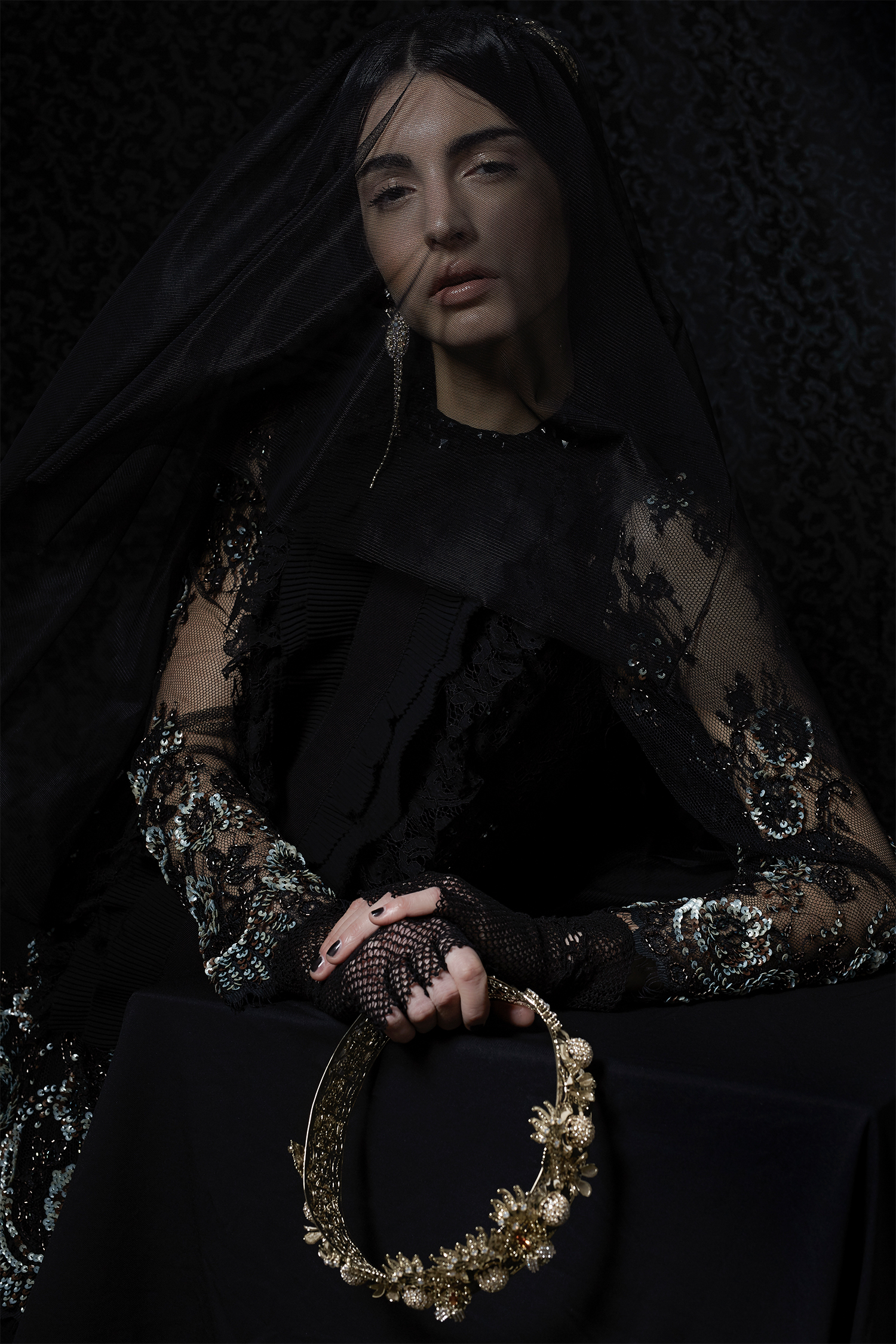 Black lace top with frills, Si-Jay; black veil dress with embroidery detail, Mori Castello; earrings and crown, Vittorio Ceccoli Jewelry