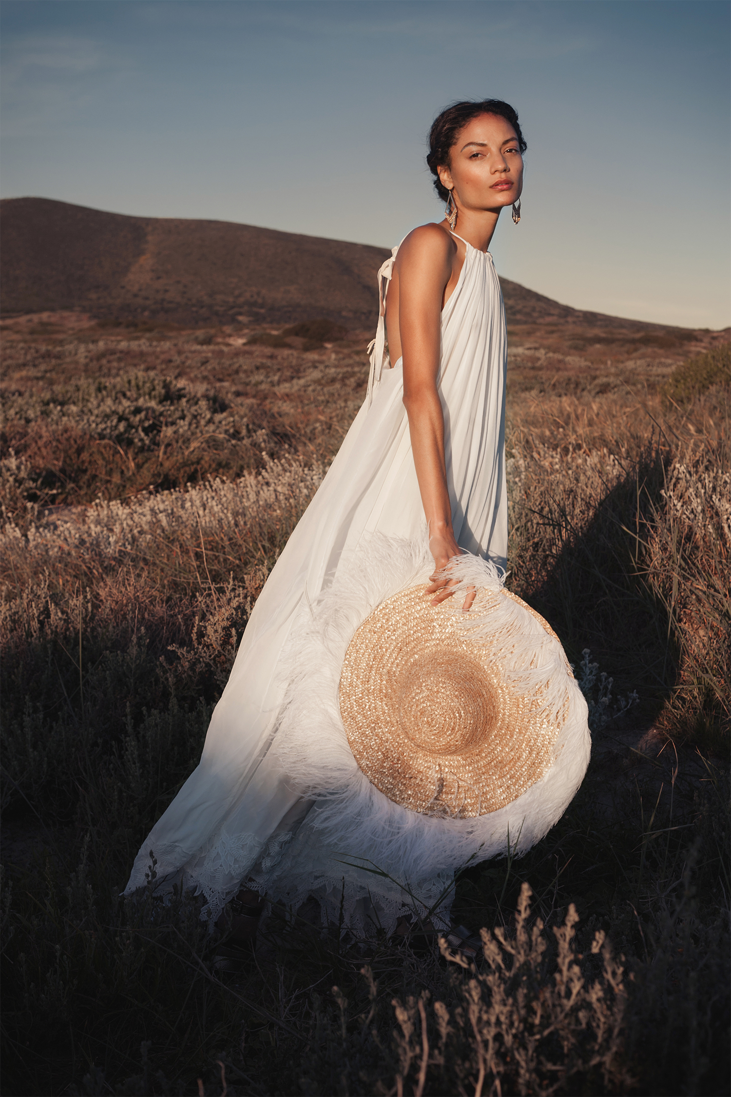 White maxi dress, Shana Morland ; straw hat with white feathers, Crystal Birch ; gold chandelier earrings, Vikki-Lou