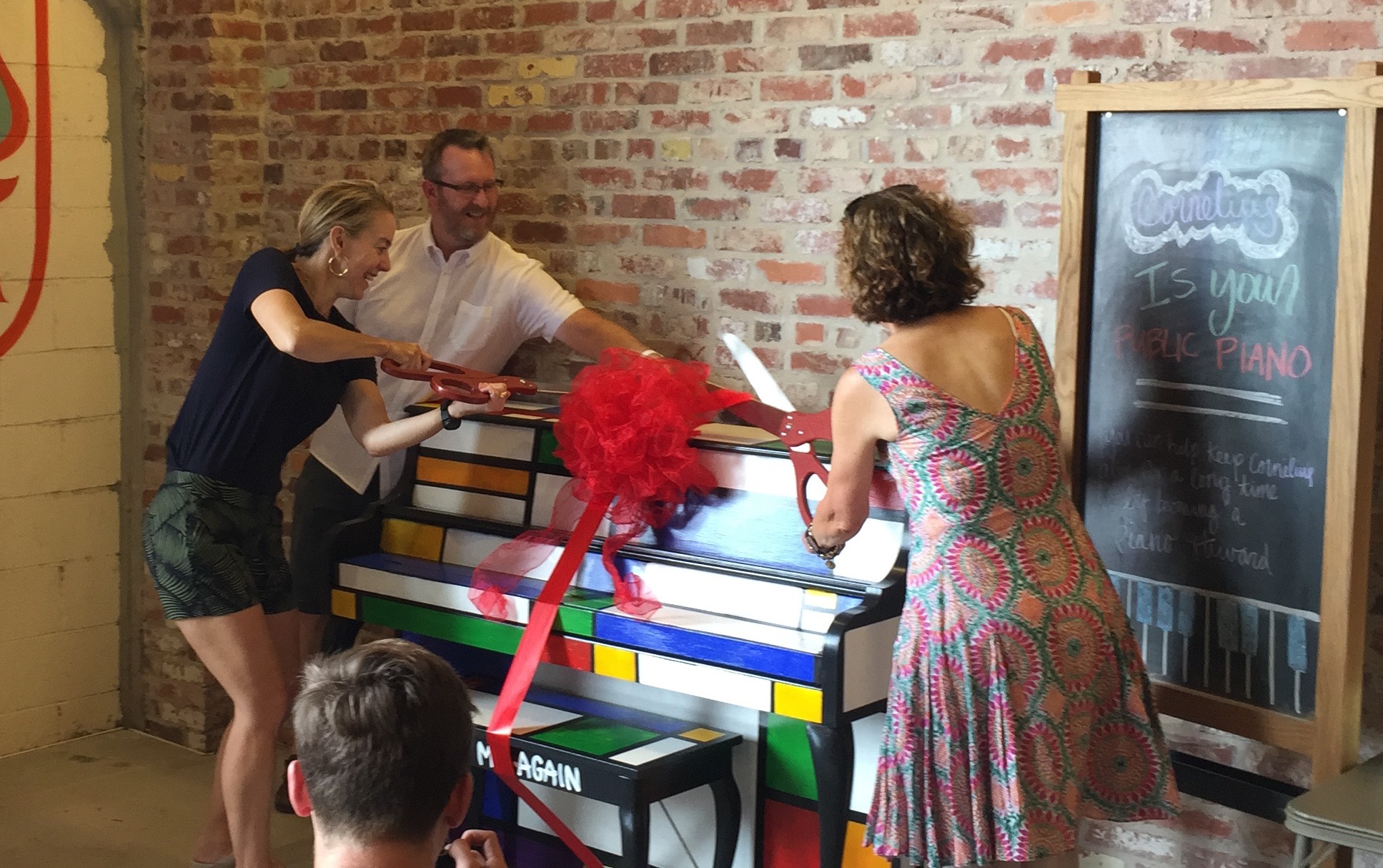 "Beth hodges (piano donor) and theresa dean (piano artists) cutting the ribbon as ""cornelius"" is introduced to ponce city market."