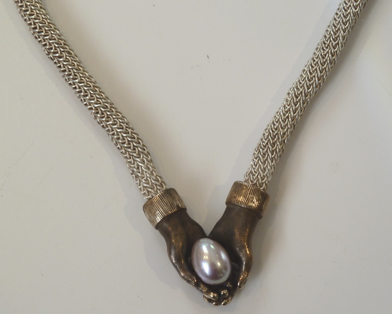 Jewelry, necklace- hand crocheted fine silver, casted bronze hands, 18k hand forged clasp and pearl egg. $3,650. .jpg