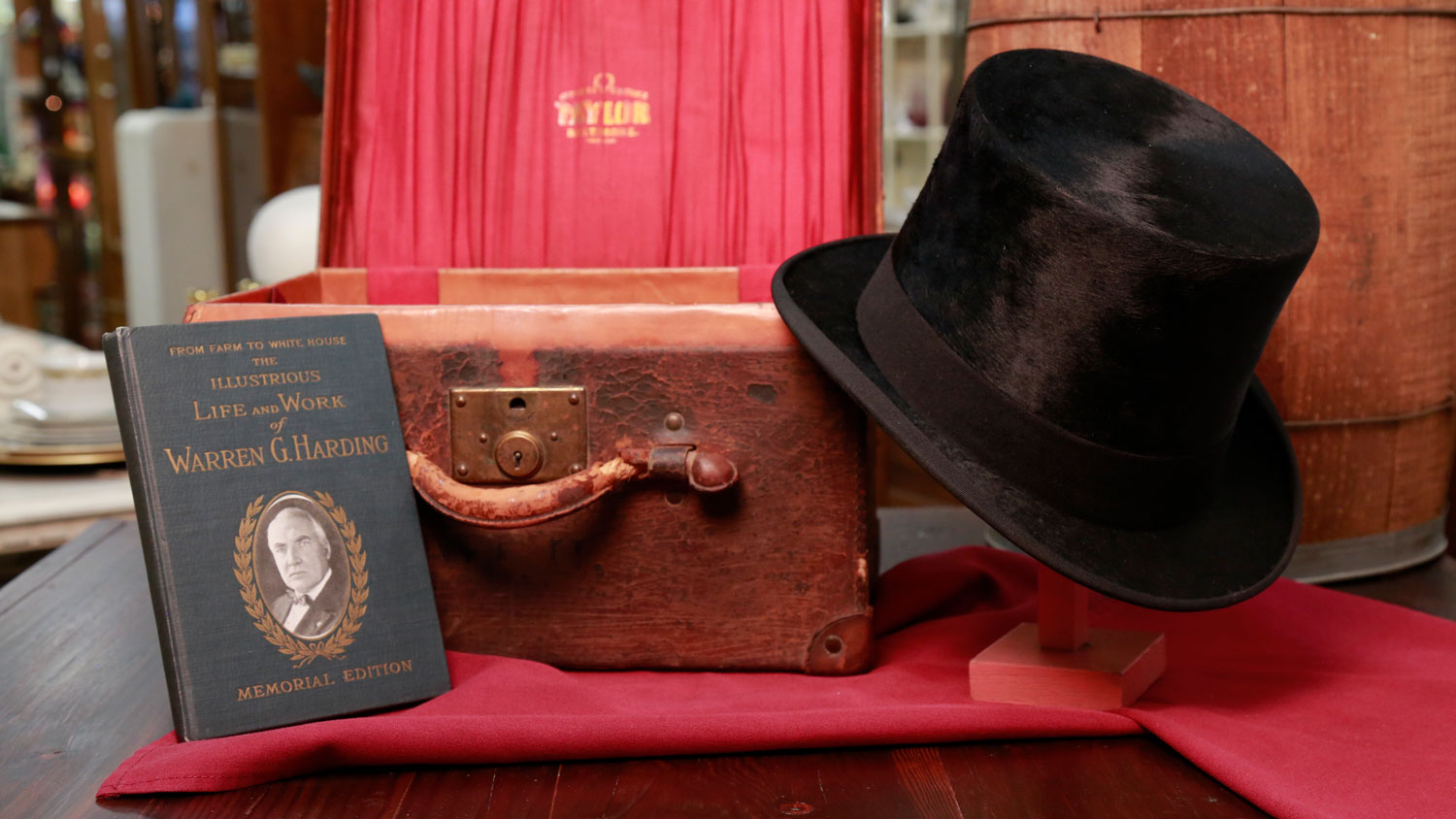 Black beaver top hat and hat box with initials WGH and a book  titled, From Farm to White House.  The Illustrious Life and Work of Warren G. Harding are shown.