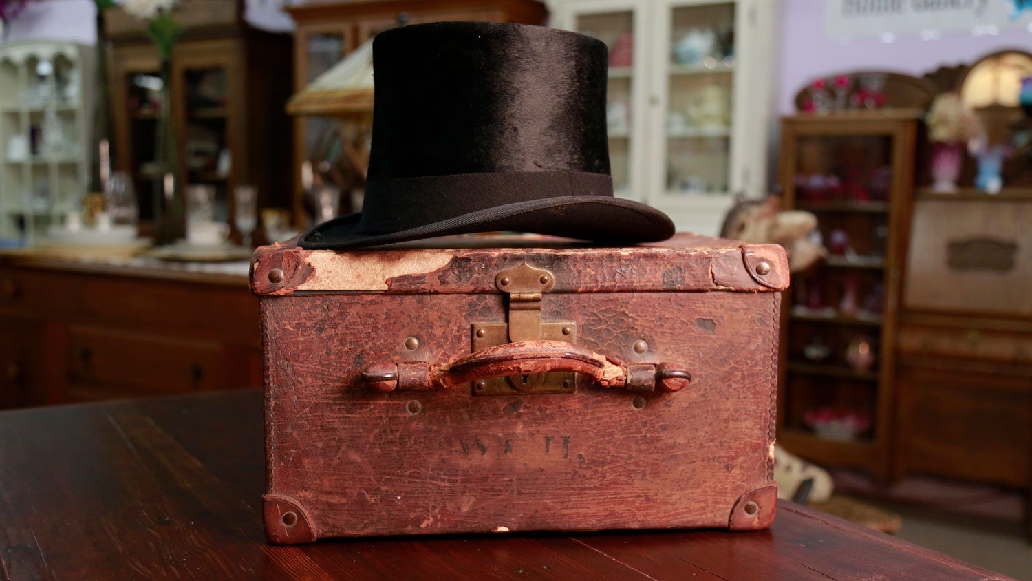 A hat box for a top hat with the worn initials W.G.H. is shown with a collectible black beaver top hat.