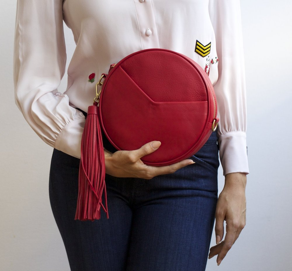 The TAH Circle Bag (in pure red) transforms into a clutch with the adjustable strap removed.