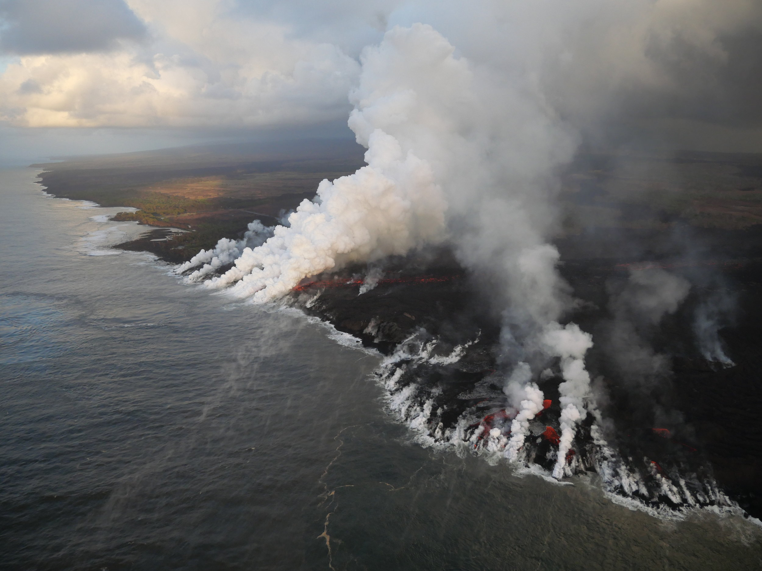 White laze plumes mark locations where lava enters the ocean over a broad area. PHOTO: USGS