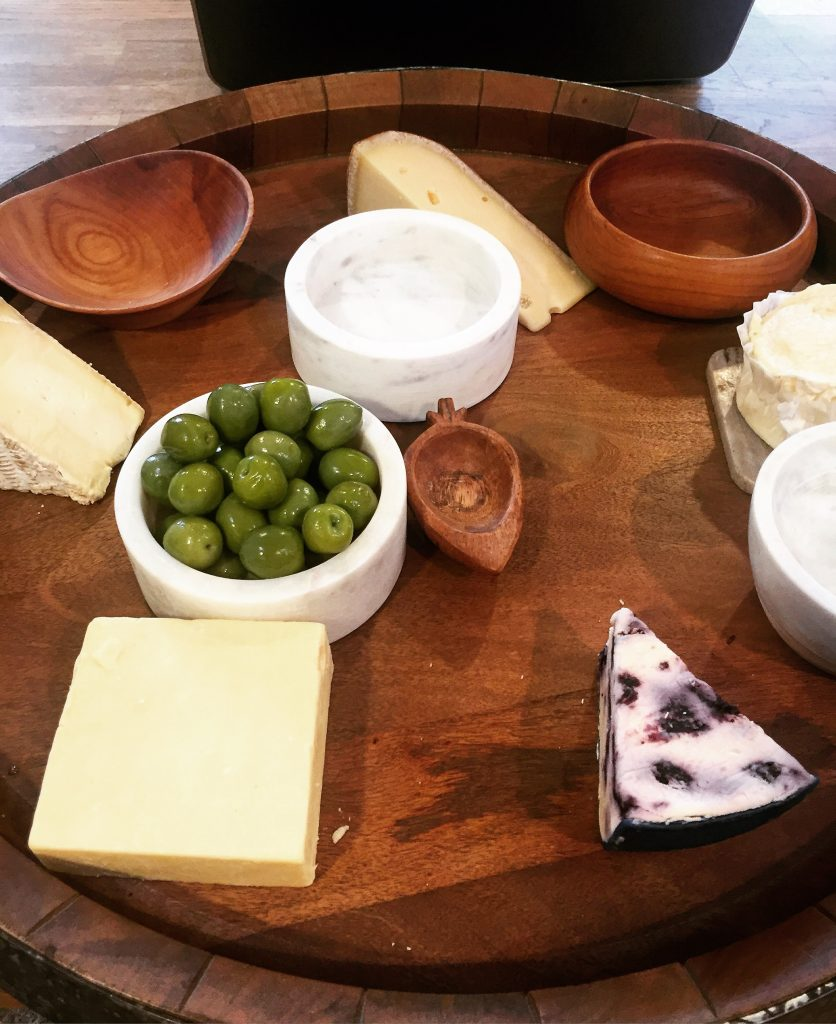 I always start out with a great base first like a big wood tray or platter. I add the largest pieces in like the cheese and place bowls with olives or honey.