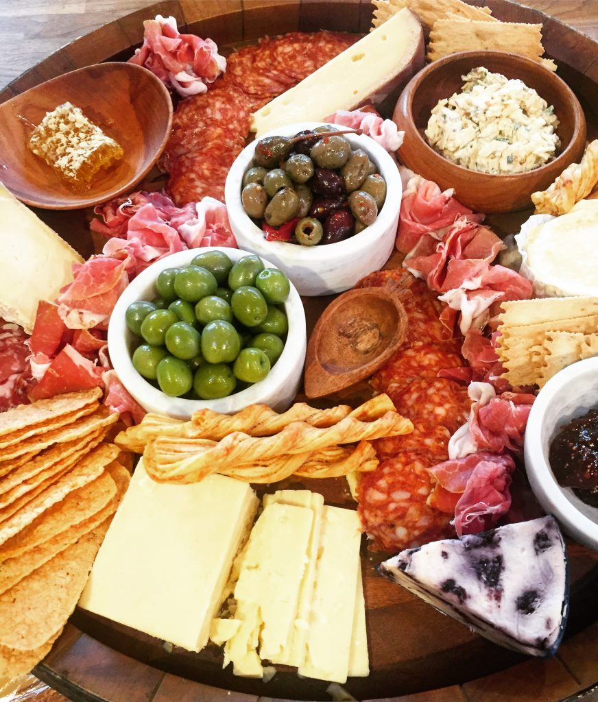 Then its all about layering! Add in rows of salami or make little bunches of prosciutto for a pretty floral look. Then add in crackers and jam into bowls. Its about variety in ingredients and color that makes a platter like this pop!