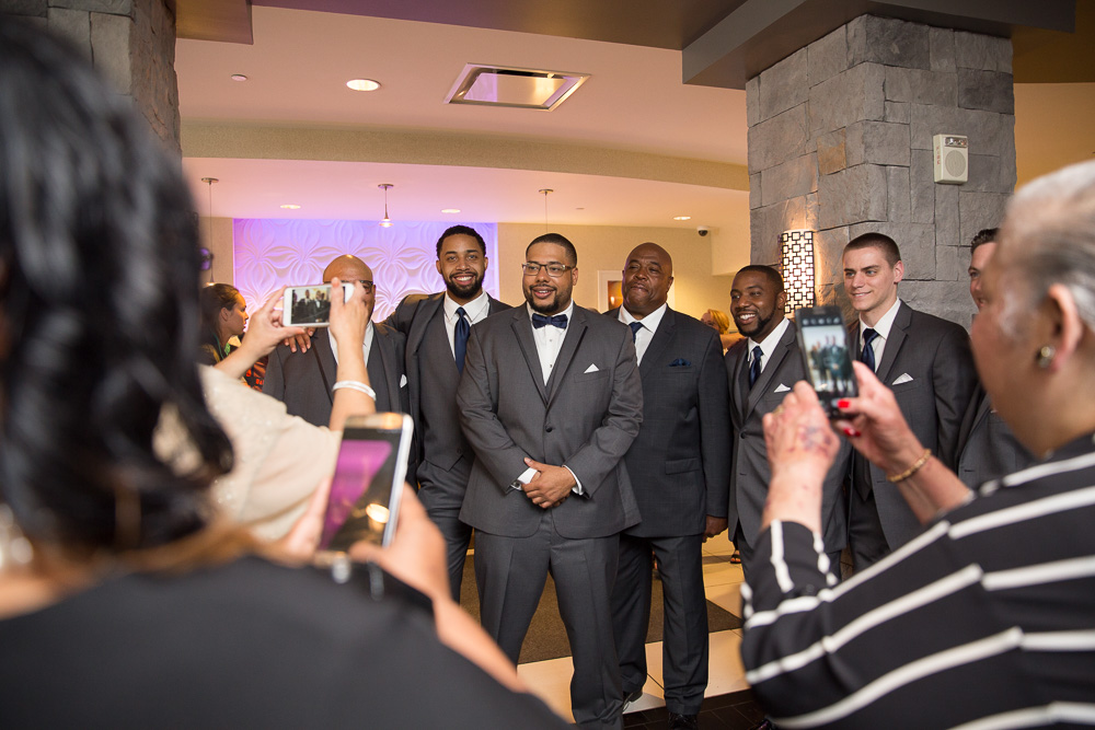 Groom and groomsmen posing for the wedding guests in the lobby of the Strathallan | Rochester, NY Documentary Wedding Photographer | Megan Rei Photography