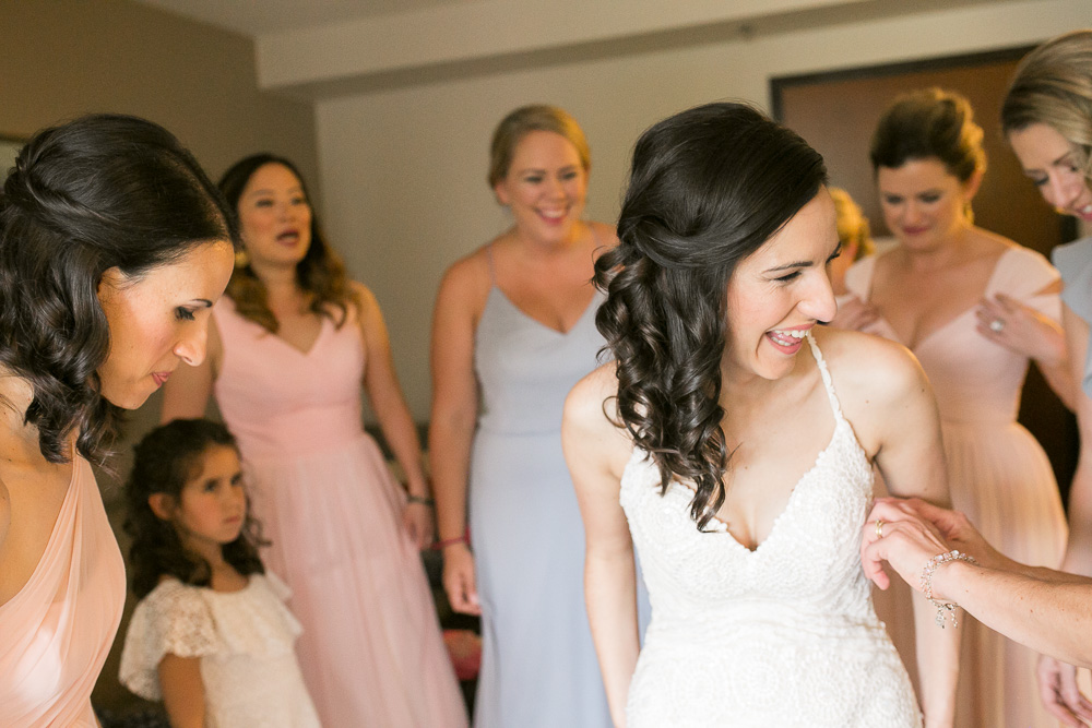 Bride laughing with her bridesmaids while getting ready | Northern Virginia Candid Wedding Photographer