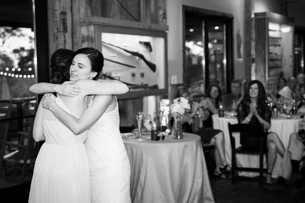 Bride and maid of honor hugging after the toasts | Candid wedding photographer in Centreville, Virginia