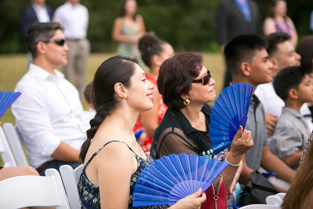 Weddings guests using their fans during the ceremony | Candid Wedding Photography in Culpeper, Virginia