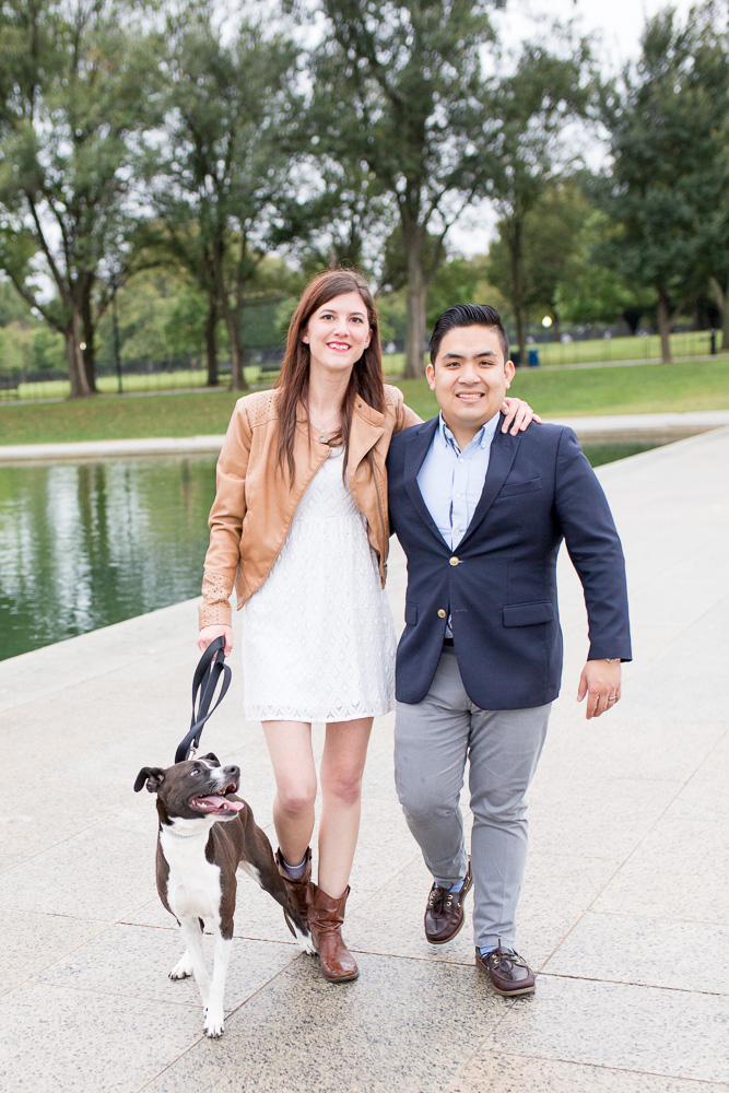 Engaged couple walking along the reflecting pool while their dog looks up at them | DC Engagement and Pet Photographer