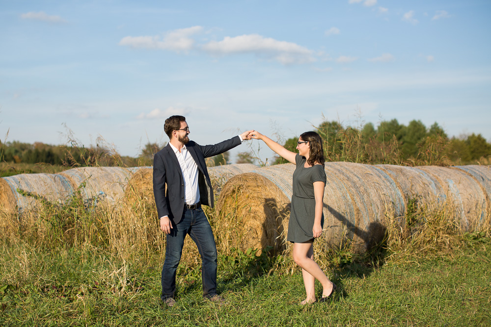 Dancing in front of bales of hay in Fauquier County, Virginia engagement shoot