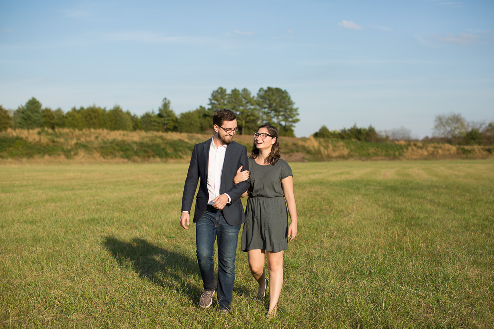 Candid engagement picture walking through field at C.M. Crockett Park